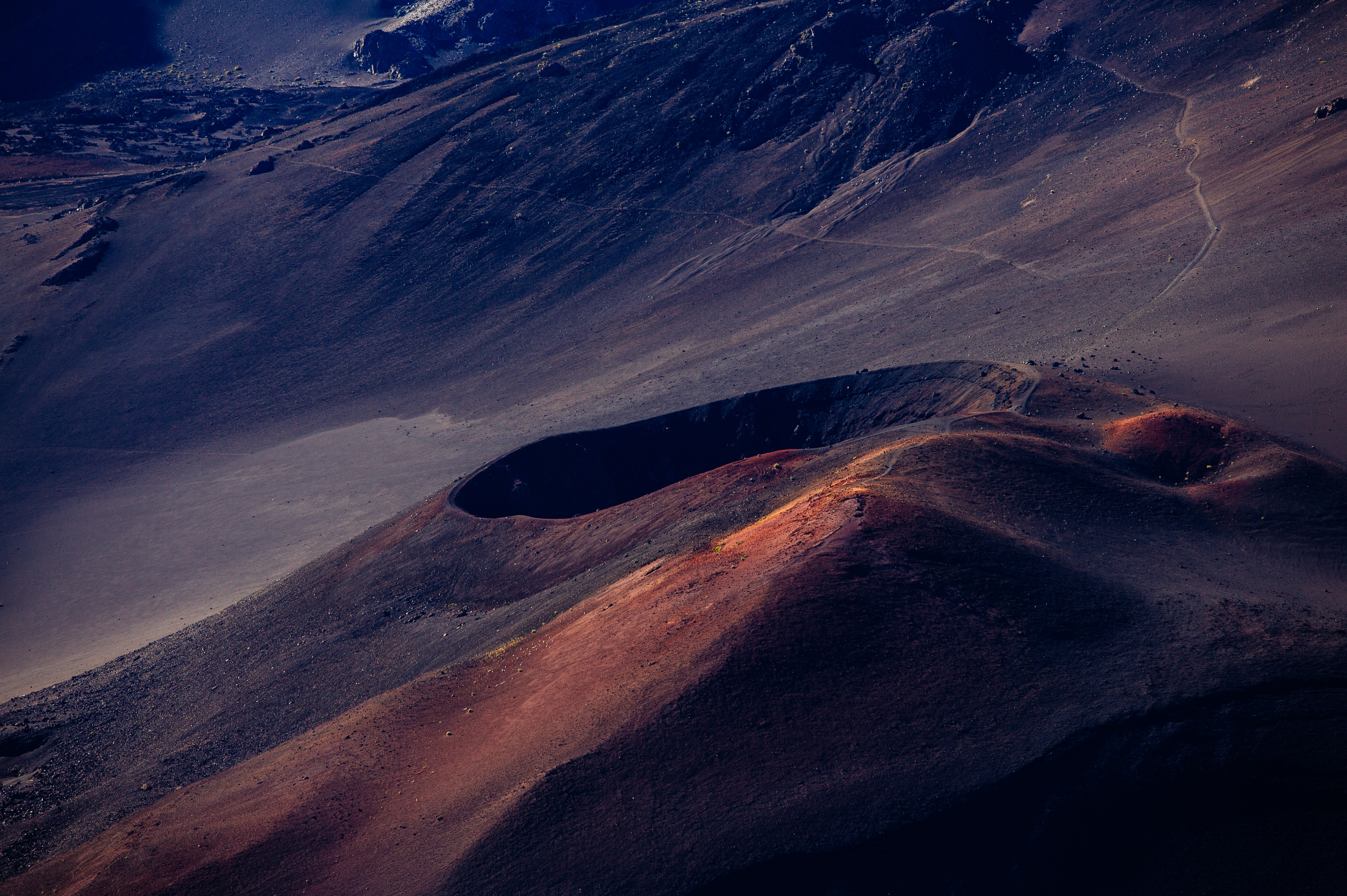 A dark blue, grey, and orange surface and crater in a volcano in Haleakala