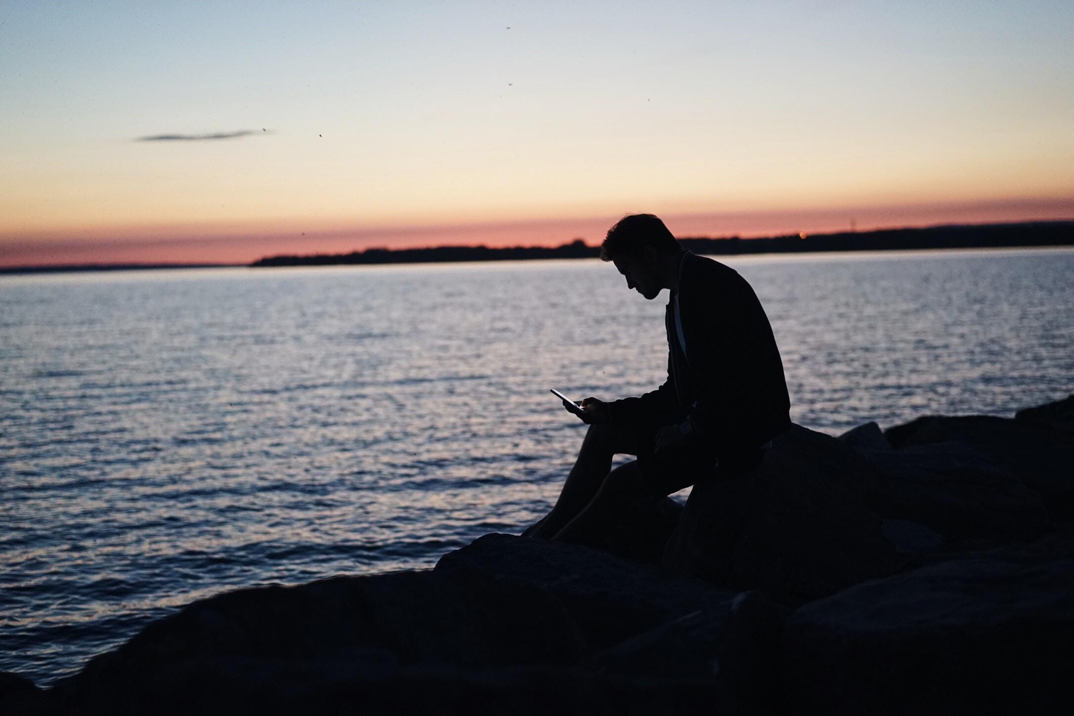 man sitting on rock in front of ocean