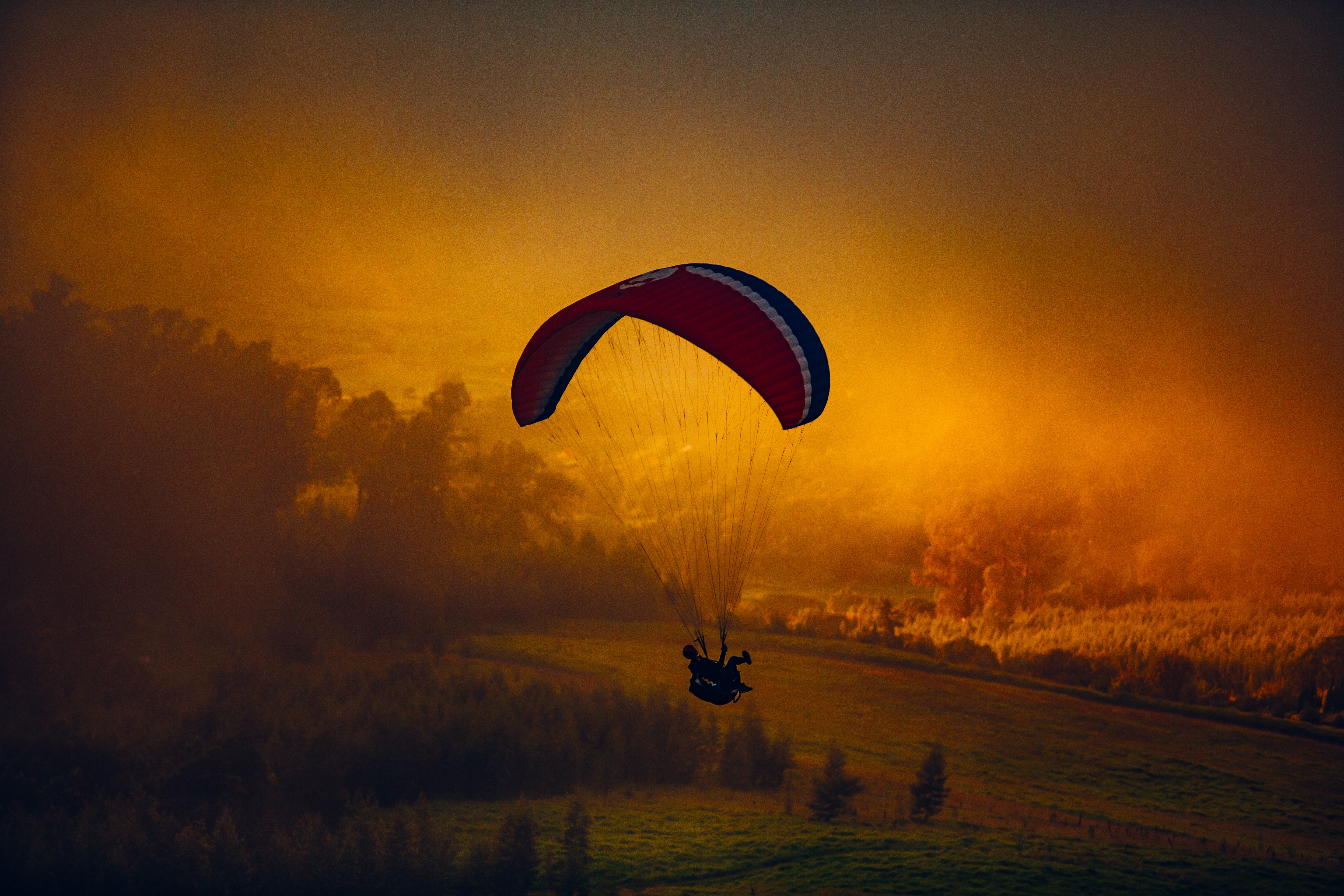 A paraglider in the air against orange-hued clouds over the countryside