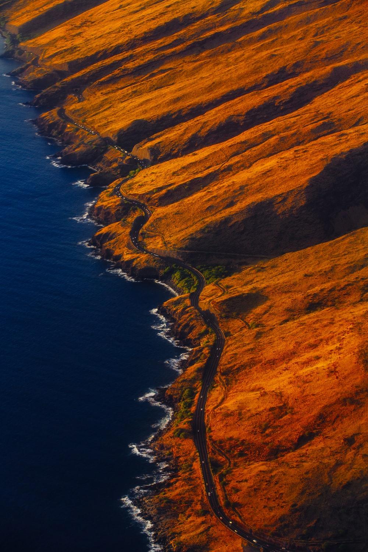 aerial photography of road on mountain near seashore
