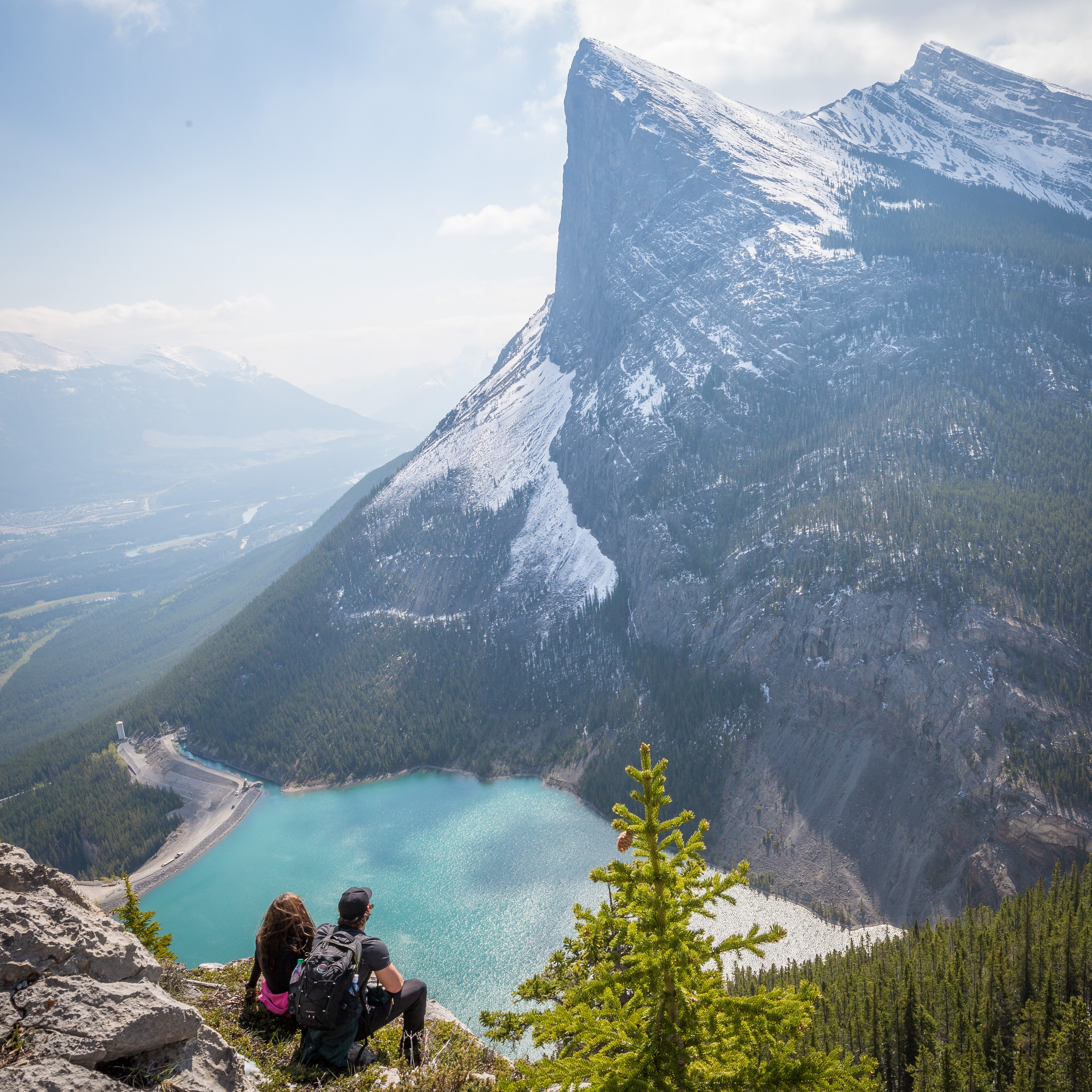 Two people sitting on a ledge high above a mountain lake in Canmore
