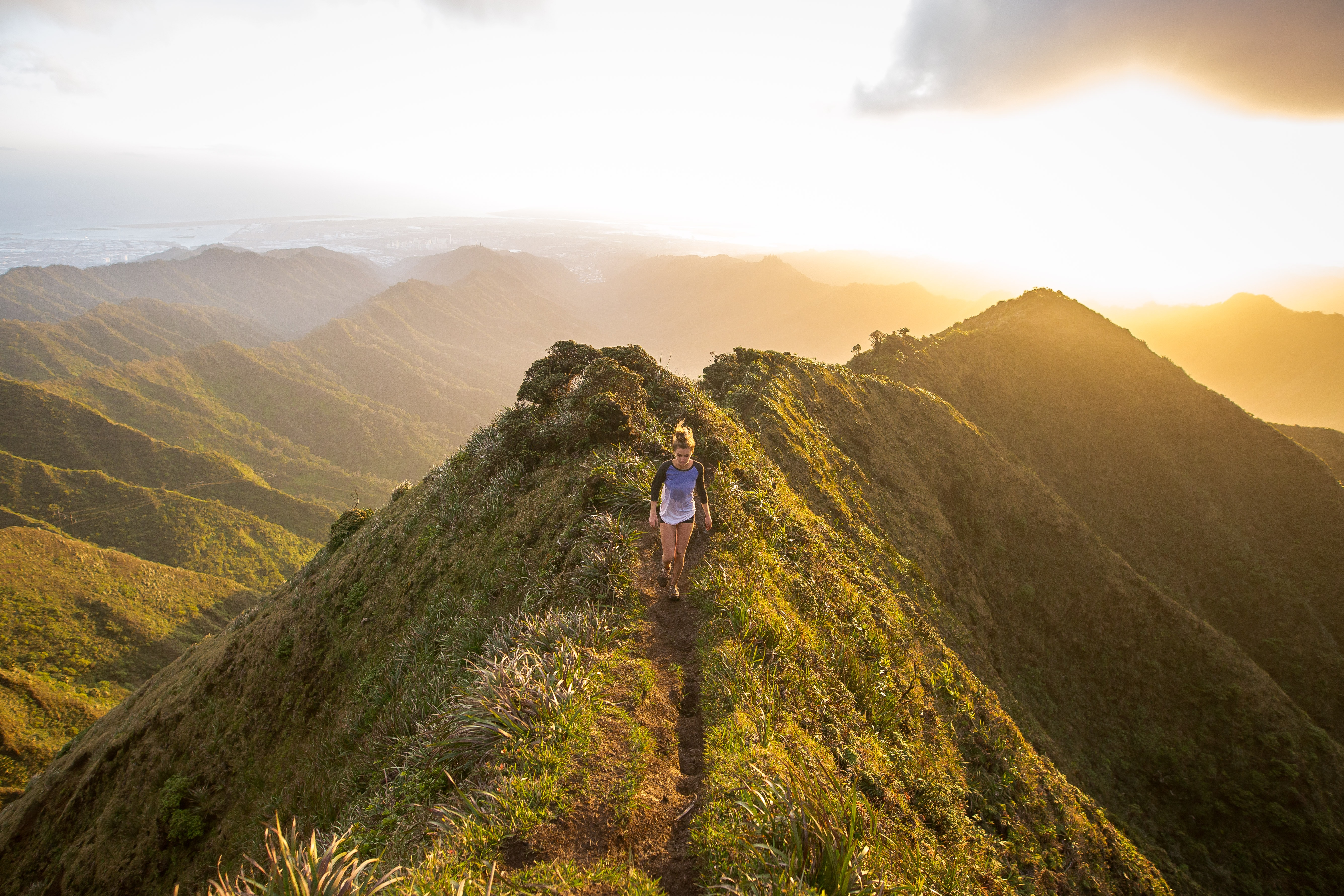 A woman hiking along the top of a grassy mountain with the sunset in the background