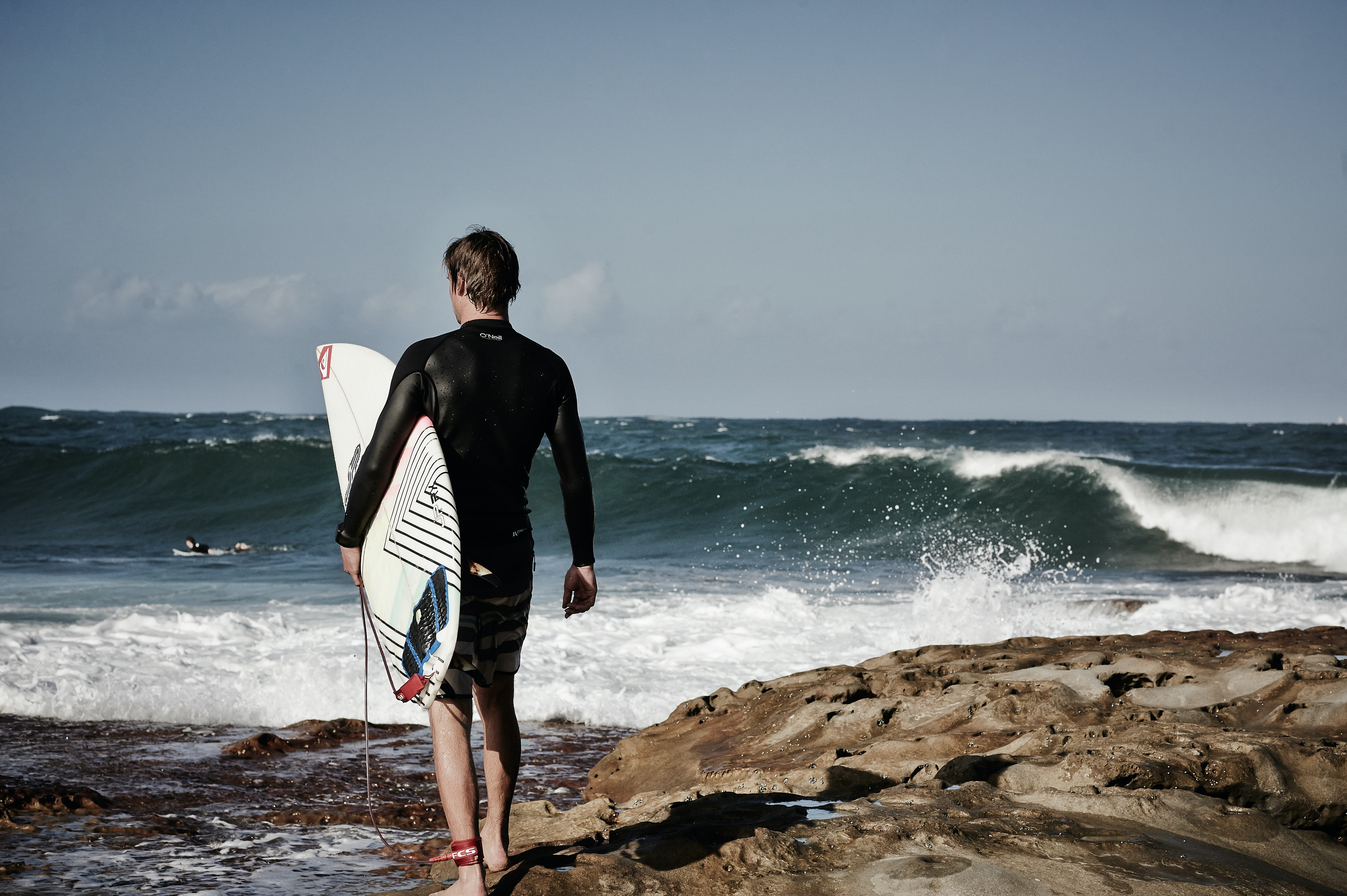 A guy wearing a wetsuit holding a surfboard looking out into the waves at Dee Why