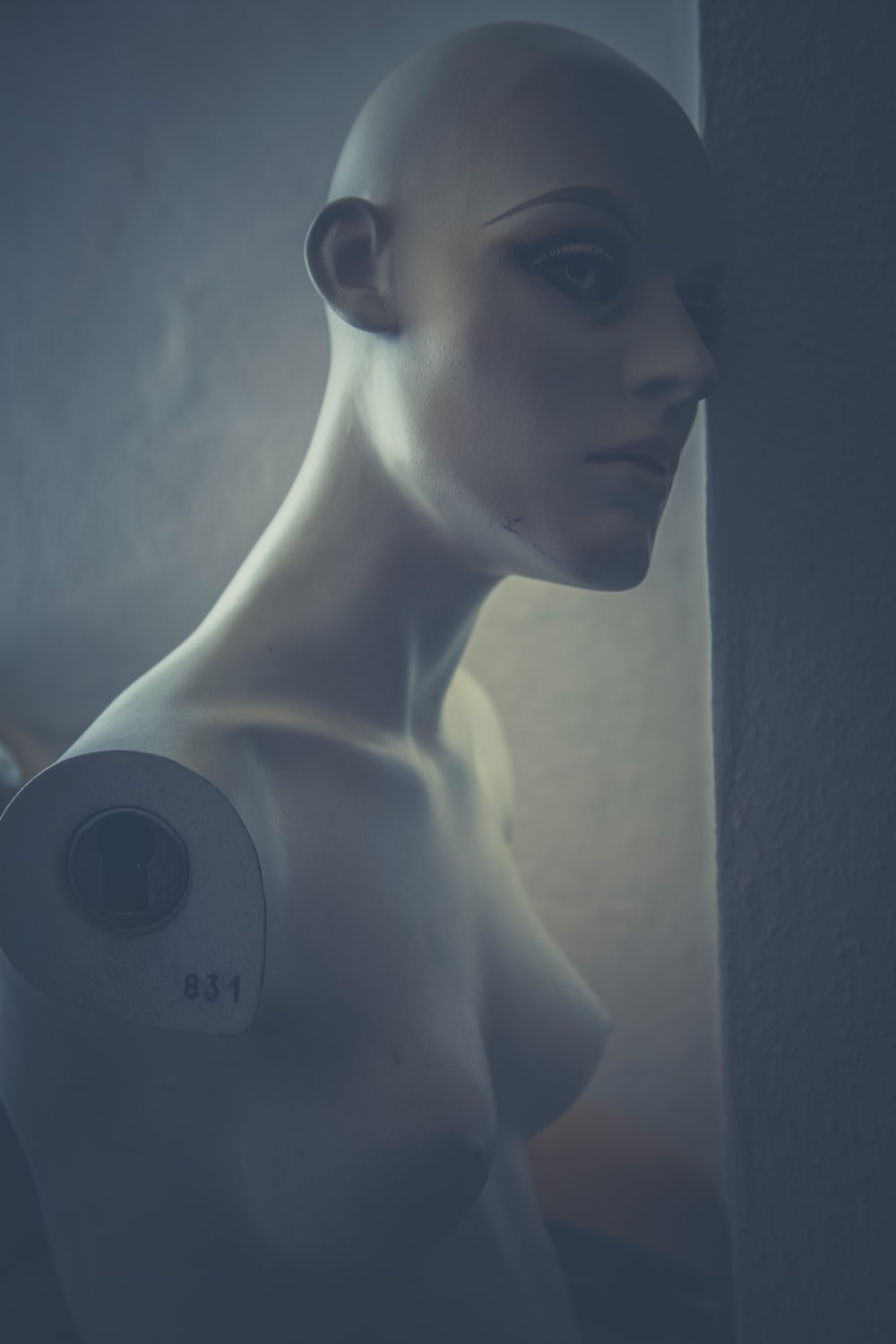 An armless mannequin with its head leaning against a wall.