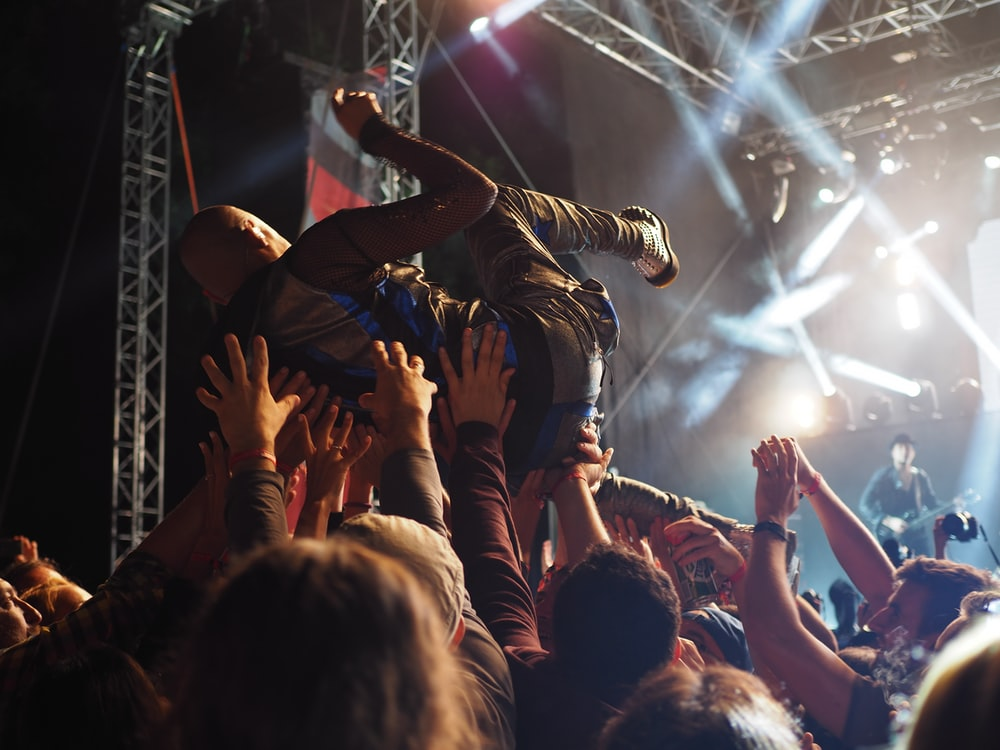 group of people carrying a person in front of the concert stage
