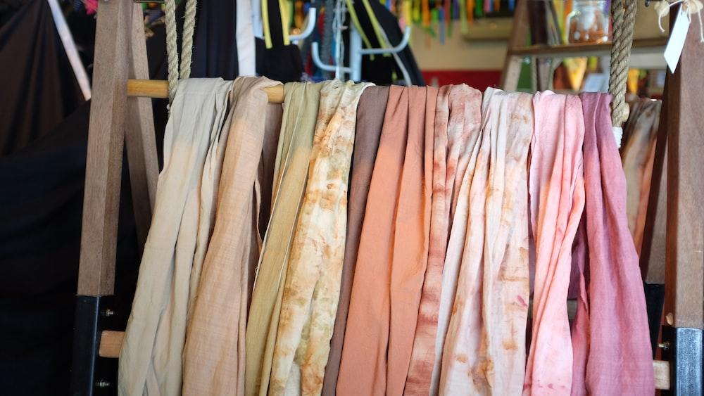 assorted scarves on brown wooden rack