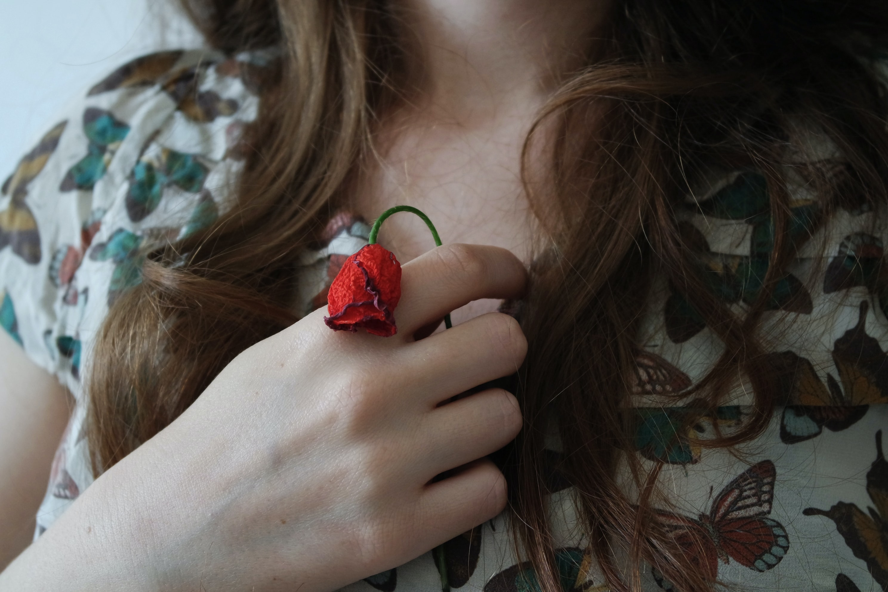 Young woman clutches a withered red rose to her heart