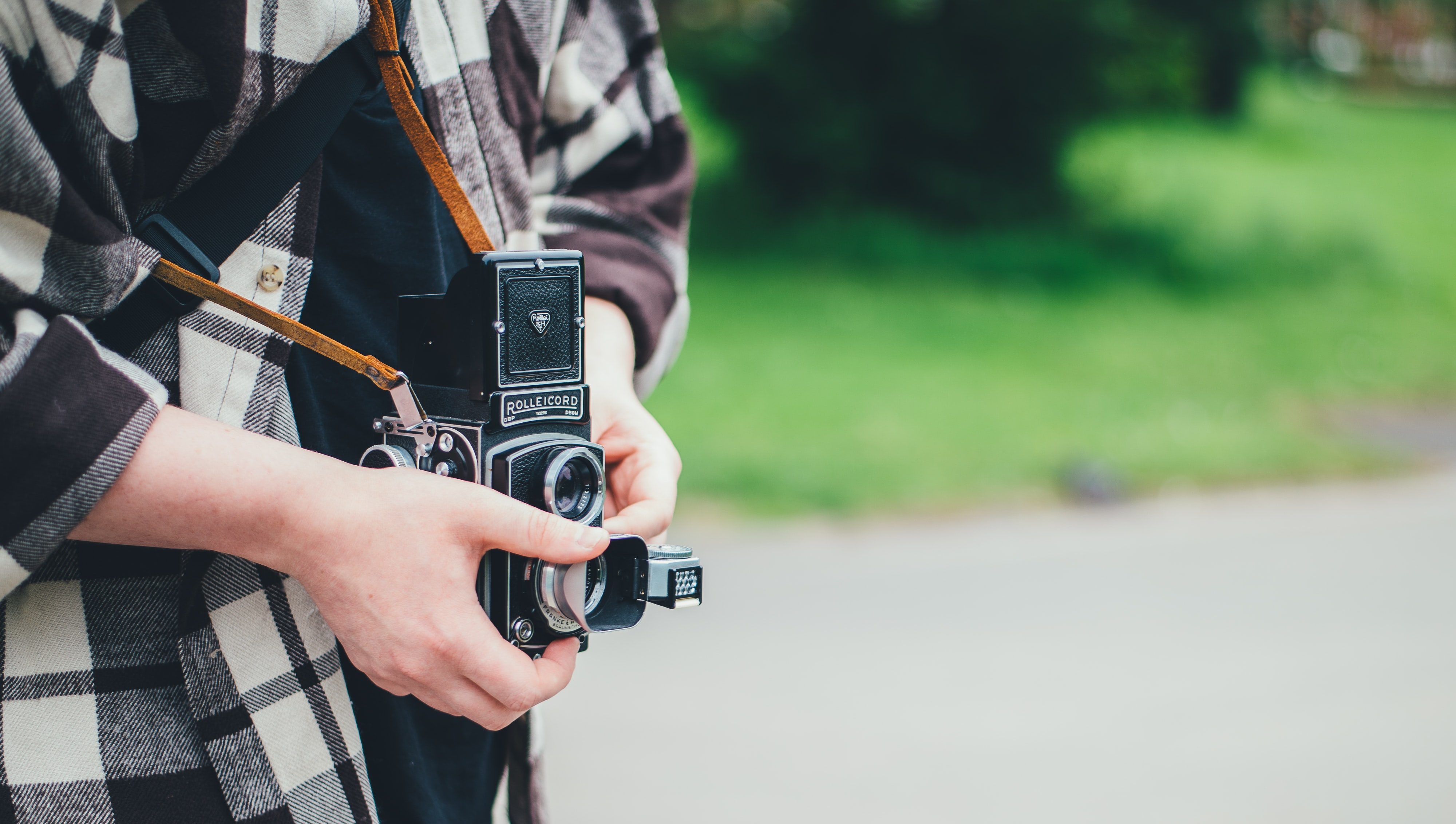 person carrying DSLR camera in shallow focus photography