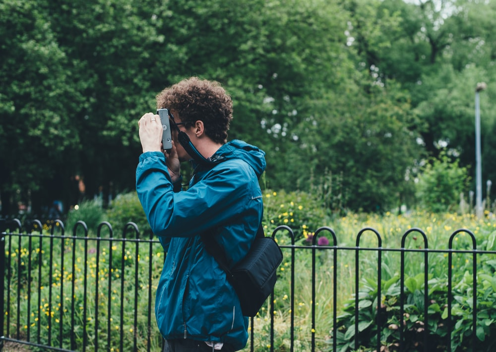 man wearing blue jacket standing and using camera beside flower field surrounded with tall and green trees