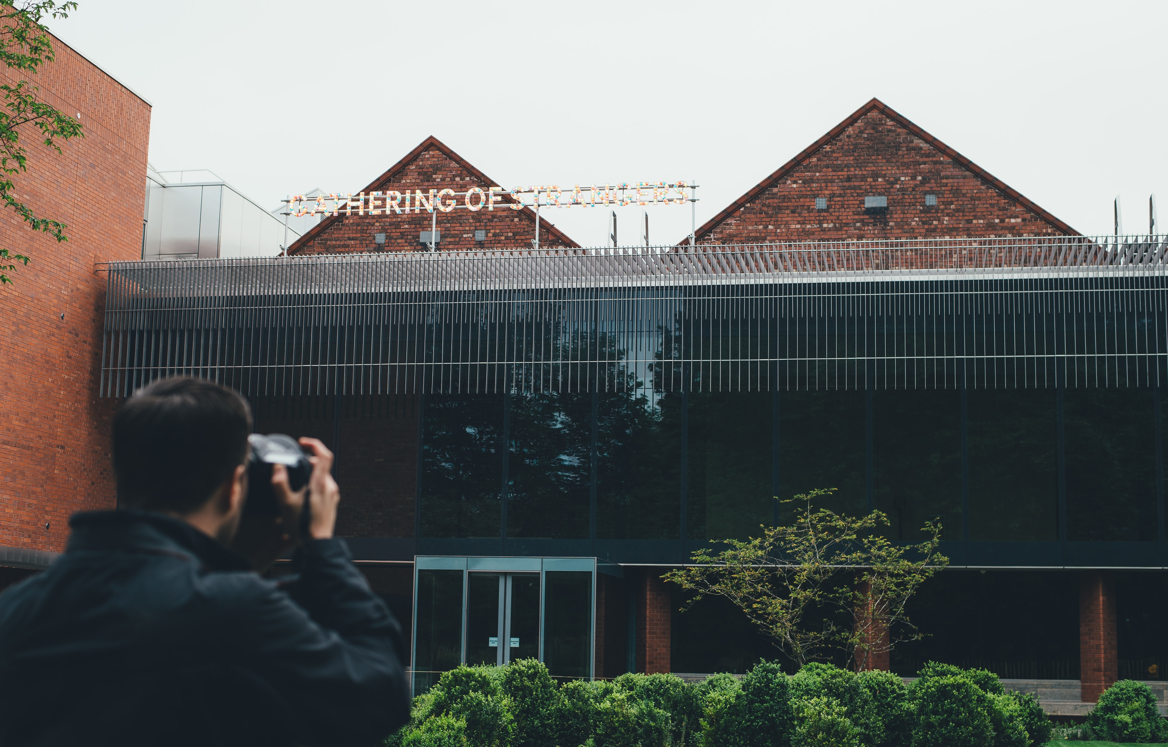 Man taking picture of gathering of strangers sign on glass roof architecture at Whitworth Art Gallery