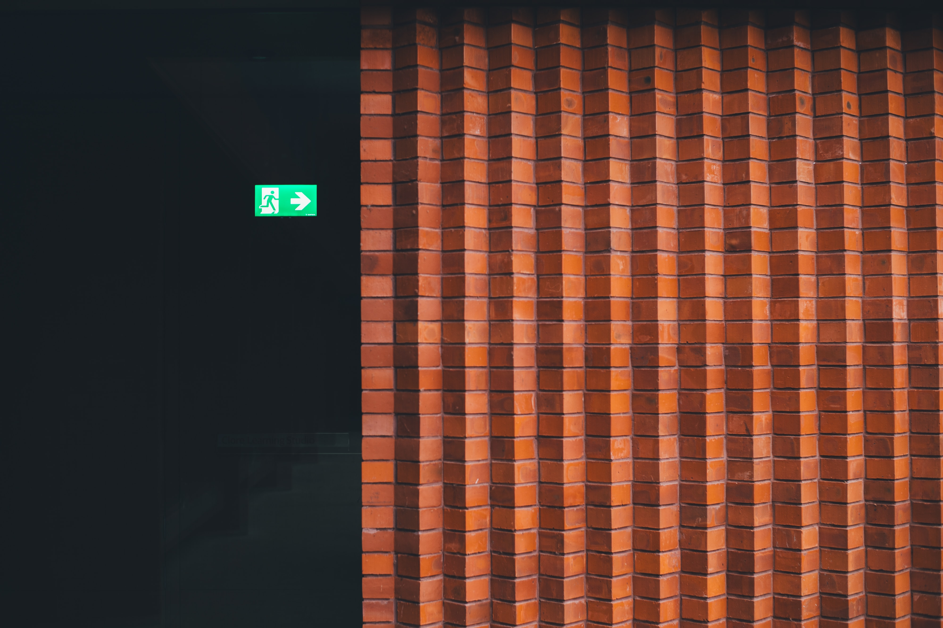 Small green exit sign pointing towards brick wall at Whitworth Art Gallery