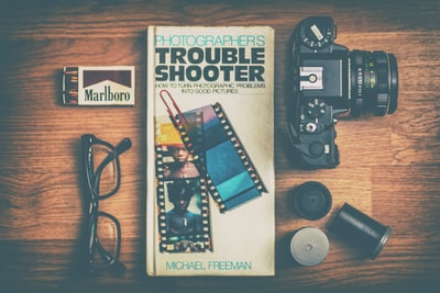 Photographers Trouble Shooter book between DSLR camera, Marlboro match box and eyeglasses