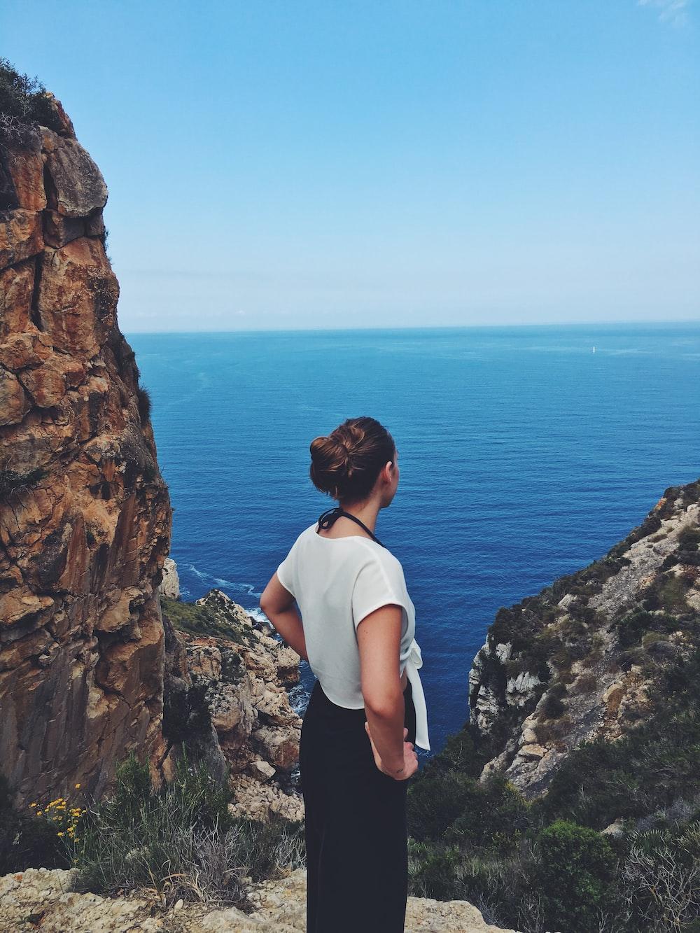 woman standing near mountain cliff