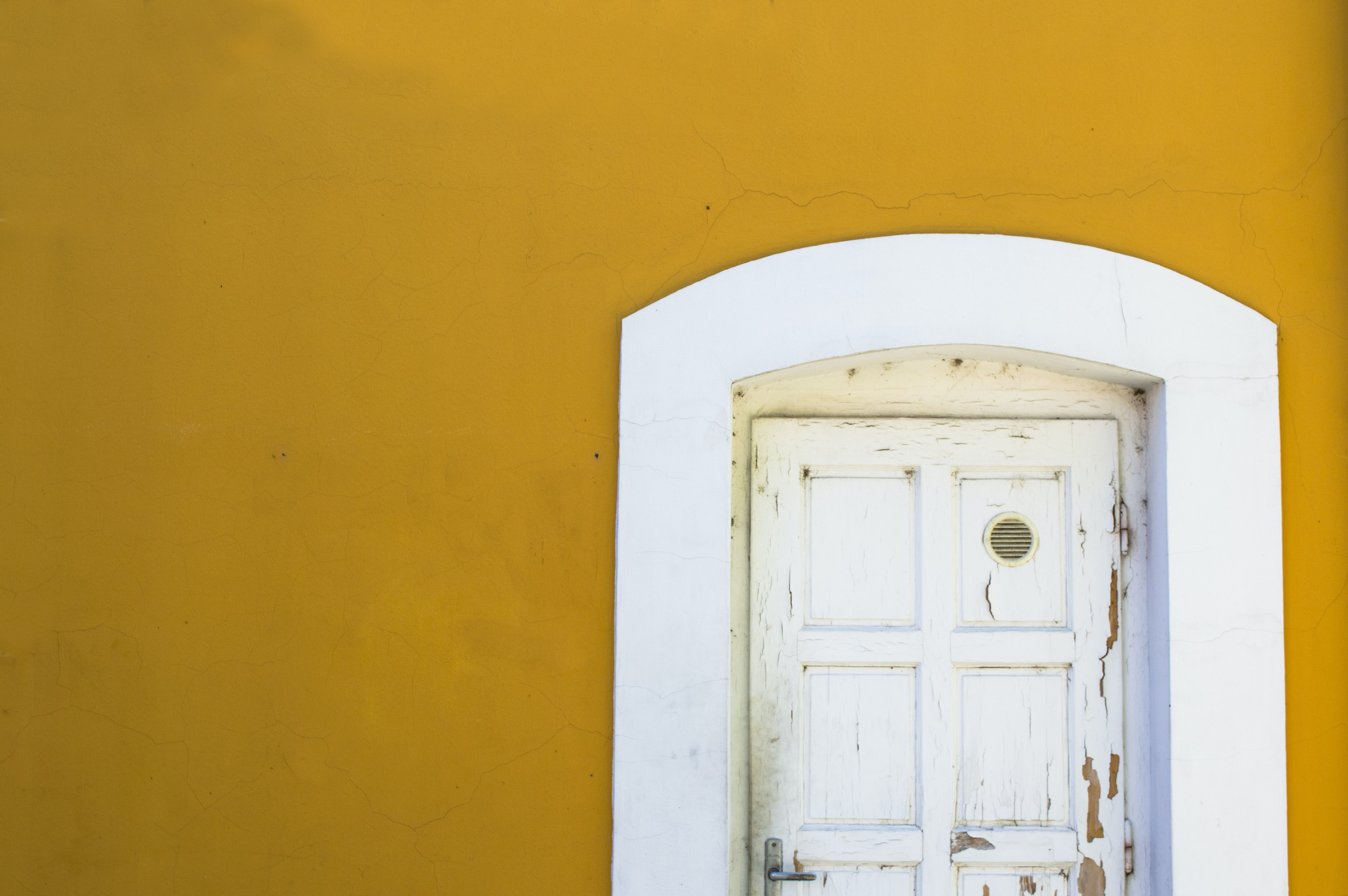 yellow wall with white wooden door