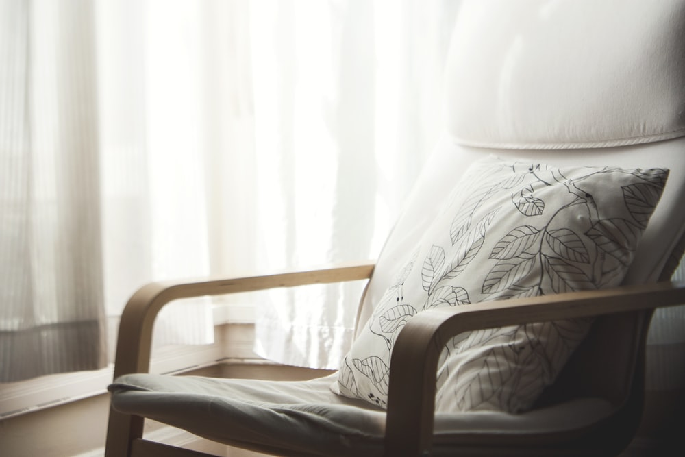 white and grey leaf-printed pillow on armchair