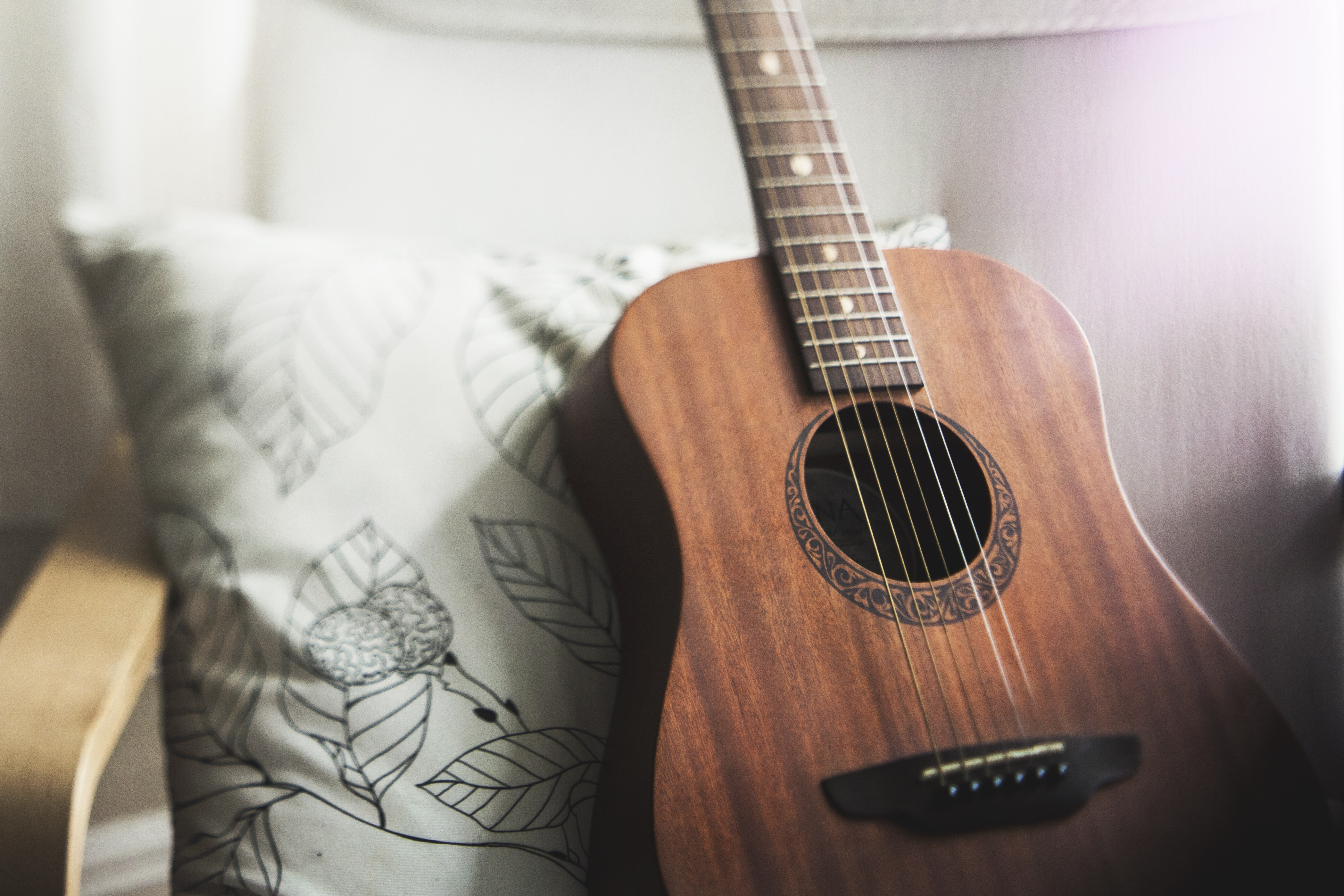 selective focus photo of brown guitar on white pillow