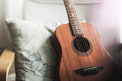 selective focus photo of brown guitar on white pillow guitar teams background