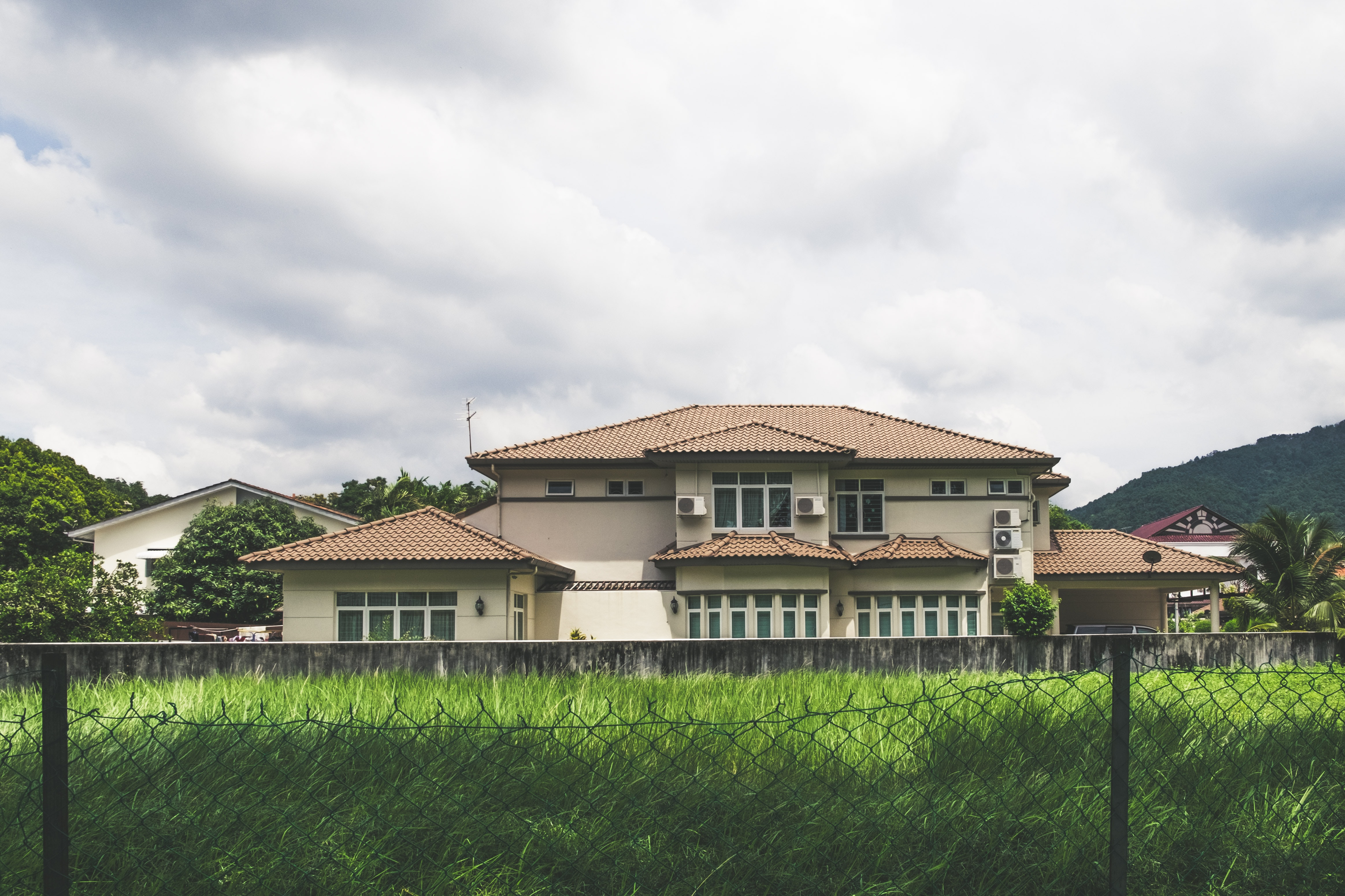 Large fenced-in house with a green grass lawn and clouds in the sky