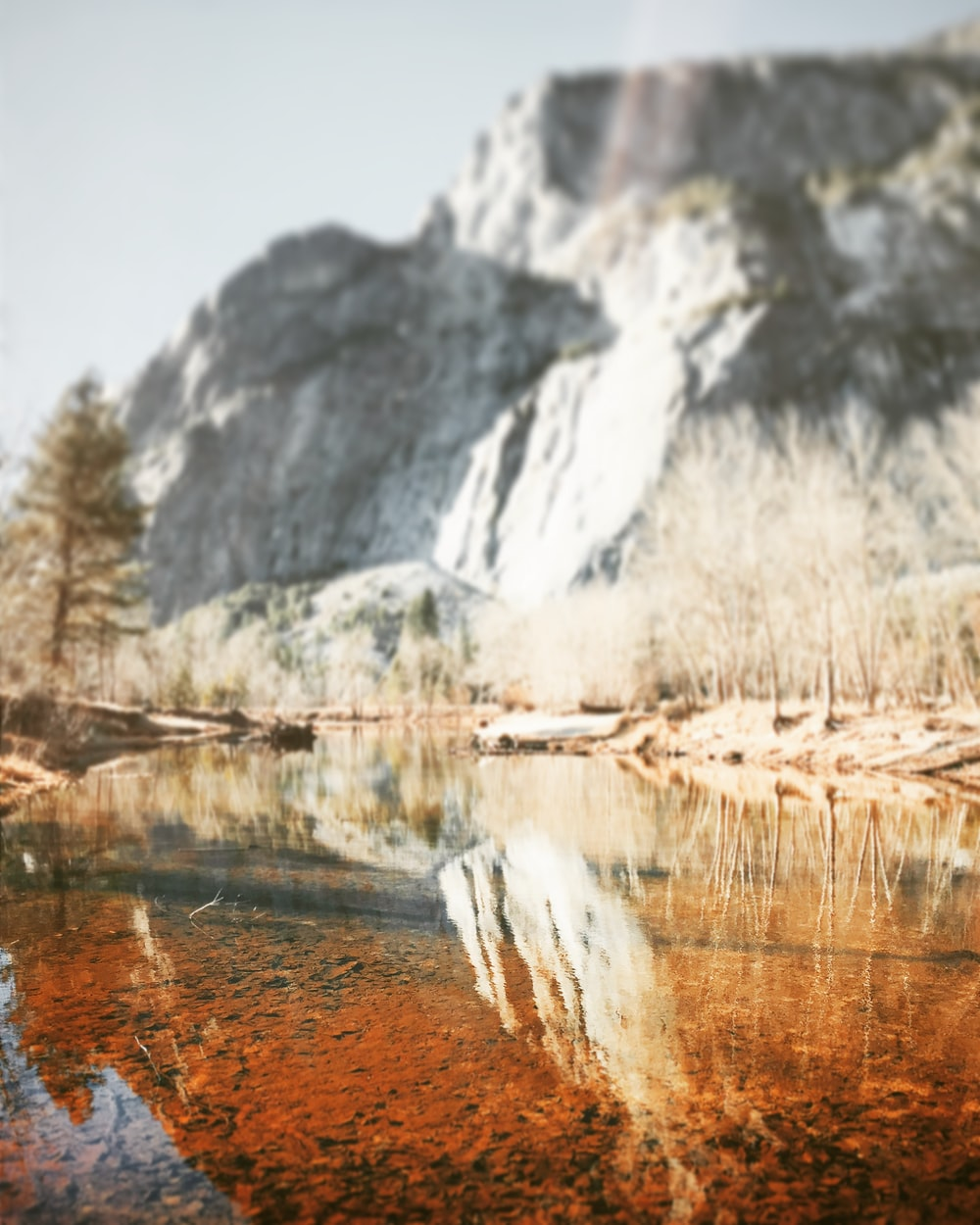 reflection of rock cliff on calm river water