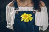 person wearing overalls with yellow petaled flowers on pocket