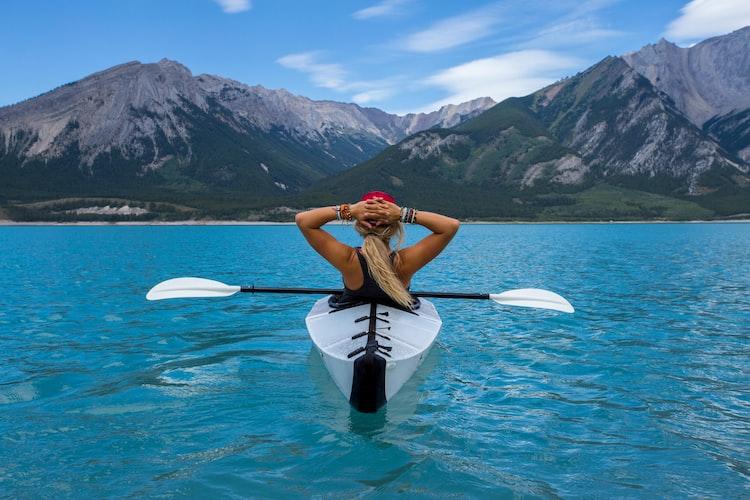 Woman relaxing in a canoe in a beautiful mountain setting