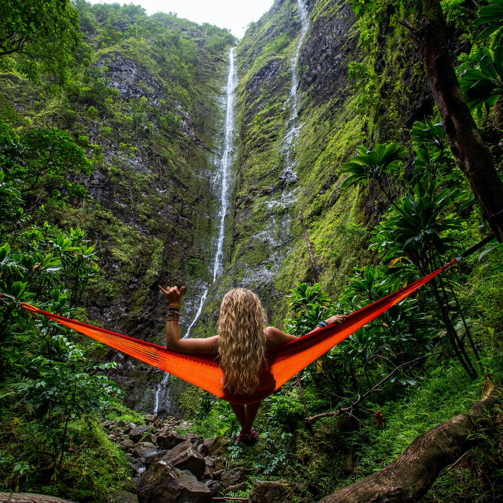 woman on hammock facing waterfalls