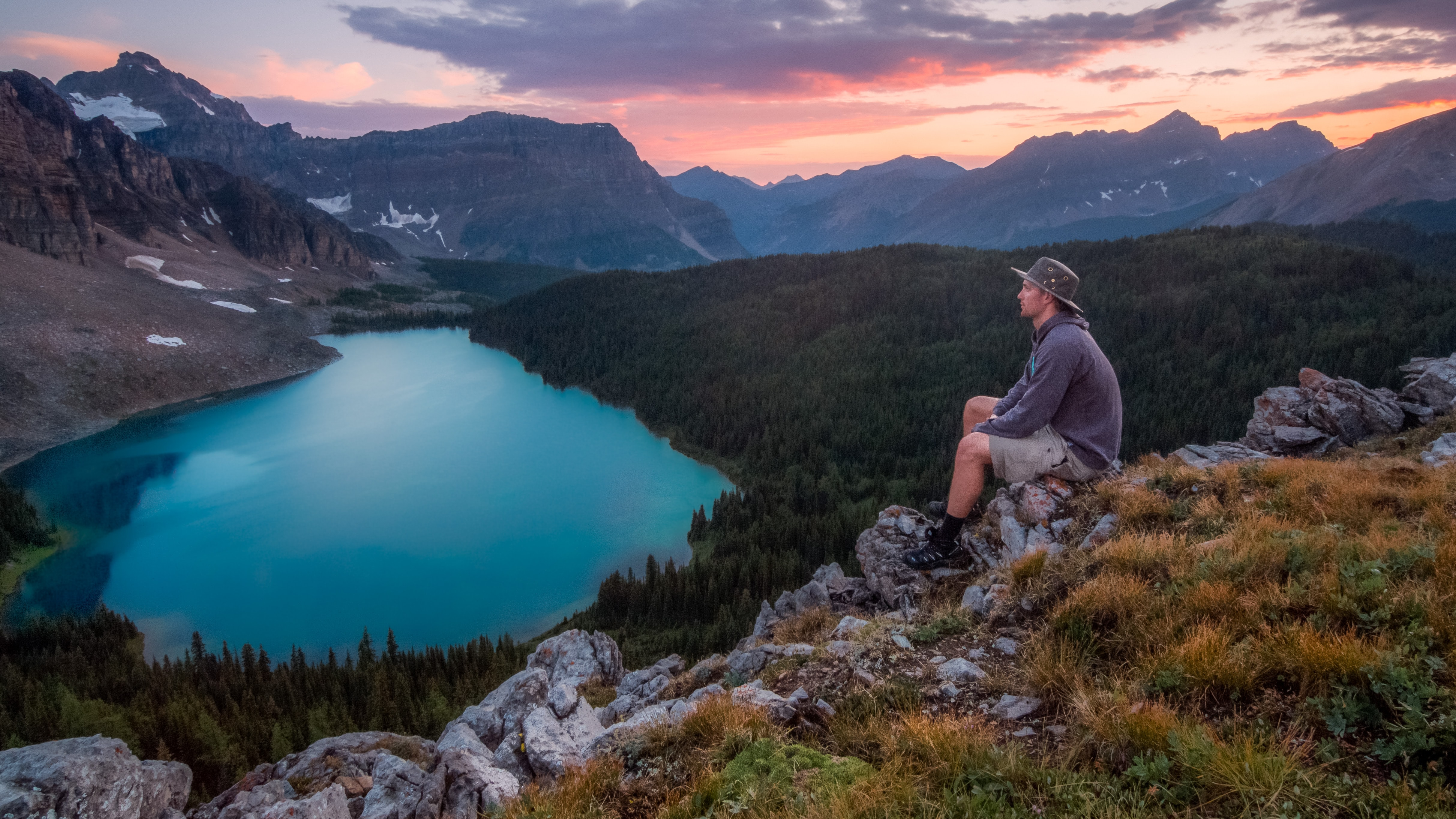 A man in a hat sitting on rocks overlooking a mountain lake