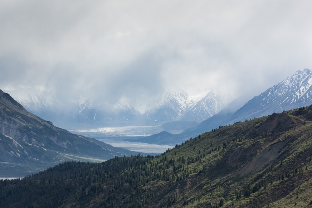 snow-covered mountains under cloudy sky
