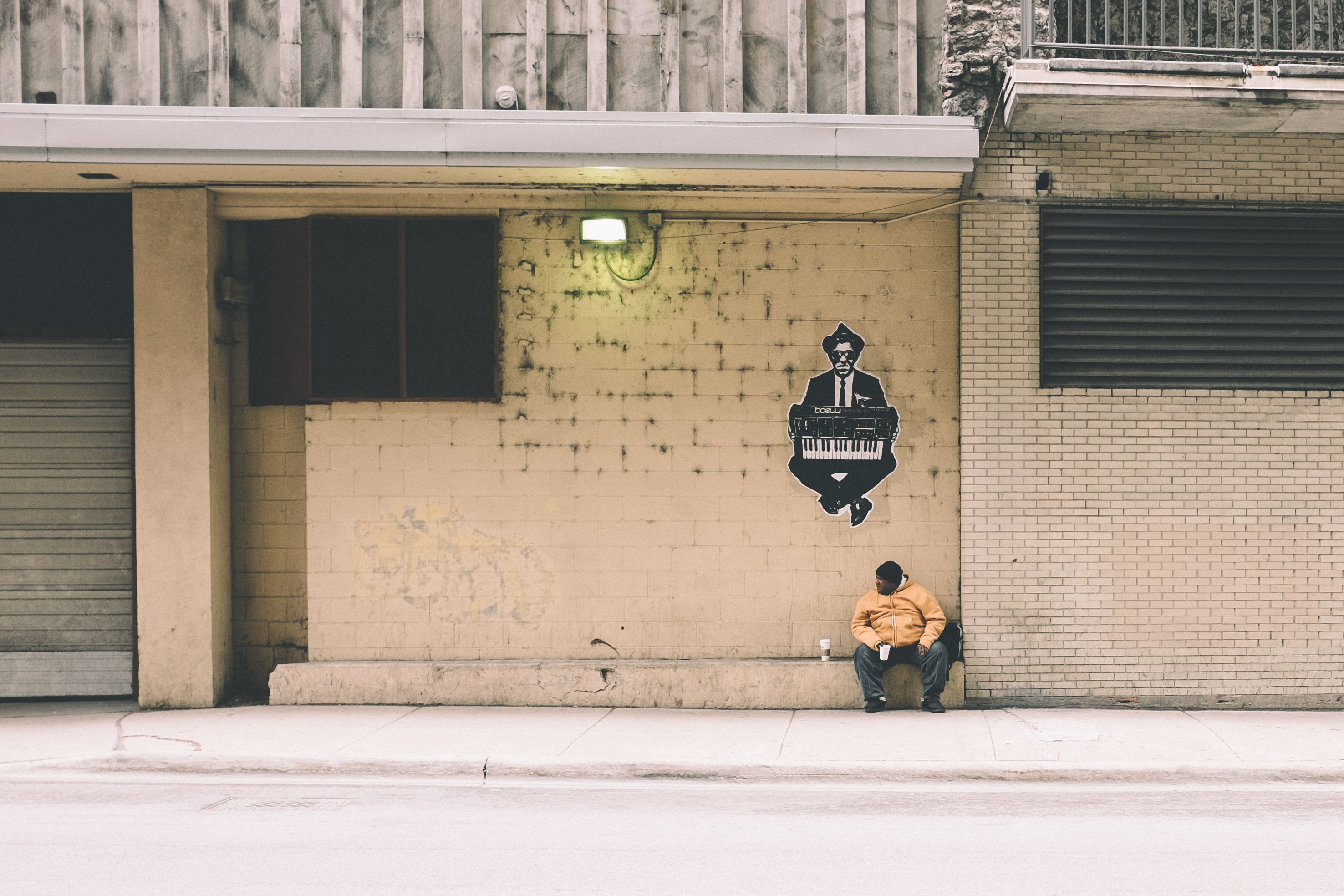 A man with a cup of coffee sitting on a ledge in the wall on an empty street