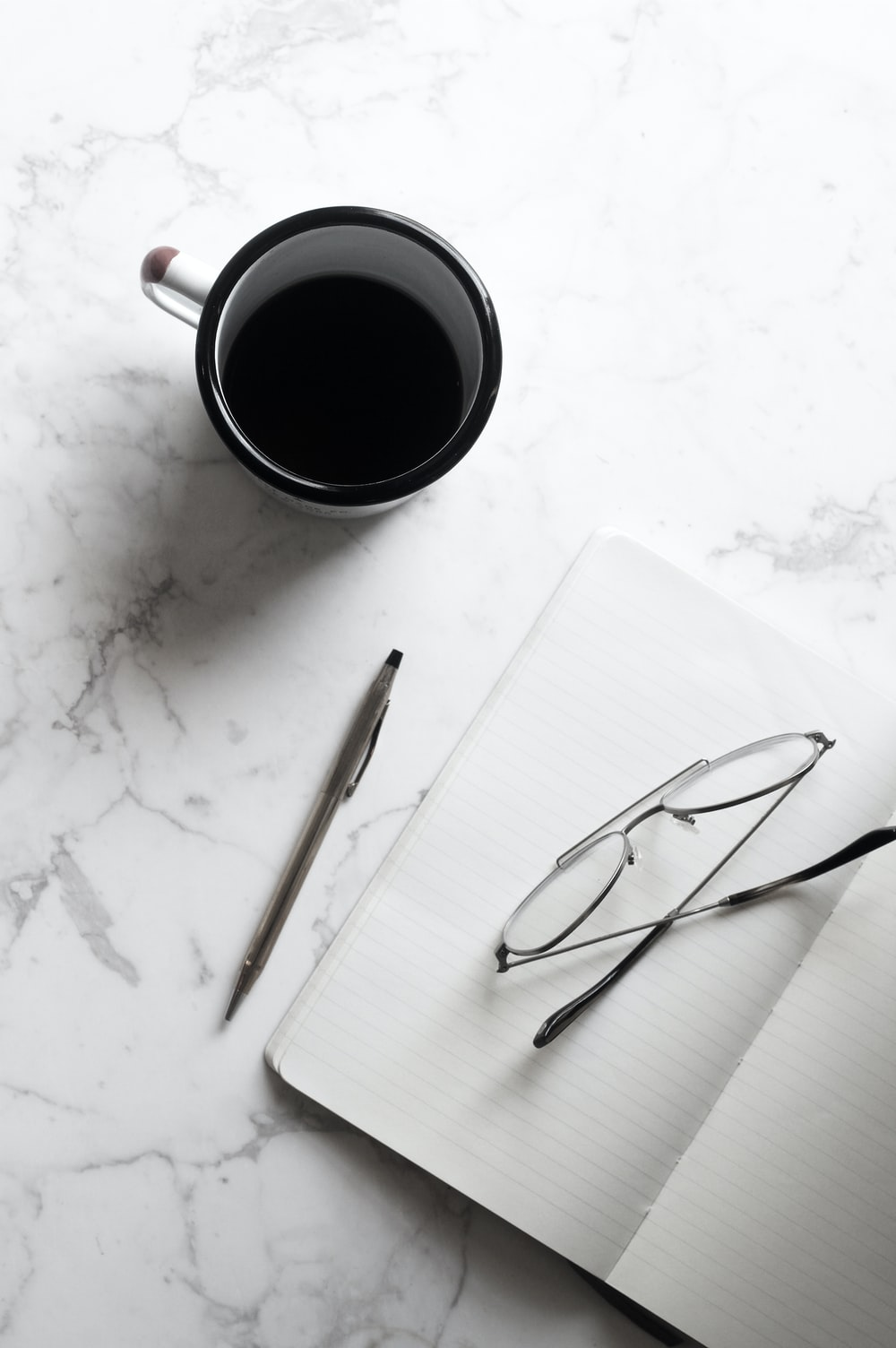 A cup of black coffee next to a notebook with a pencil and pair of glasses.