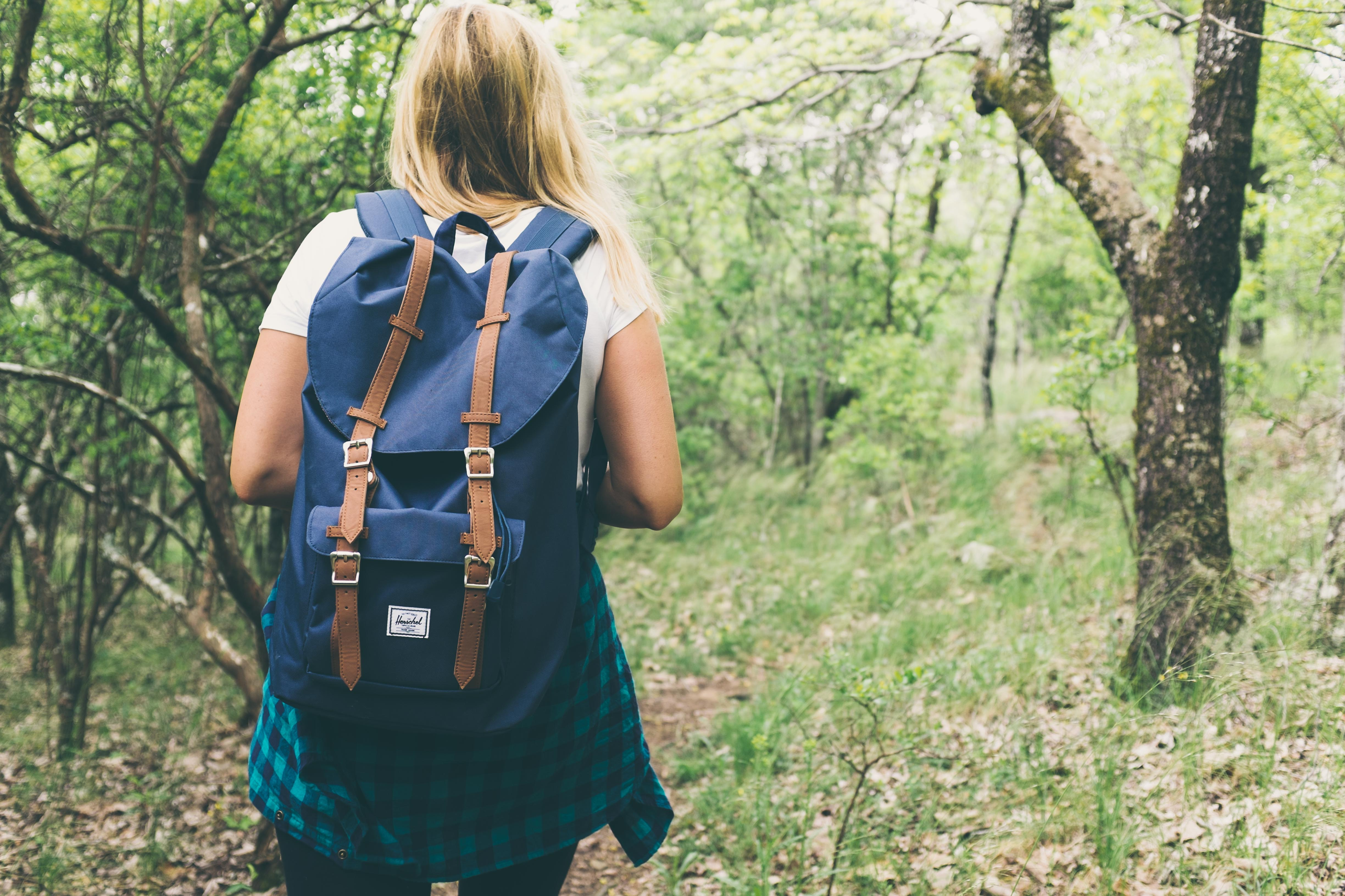 woman wearing backpack walking on forest