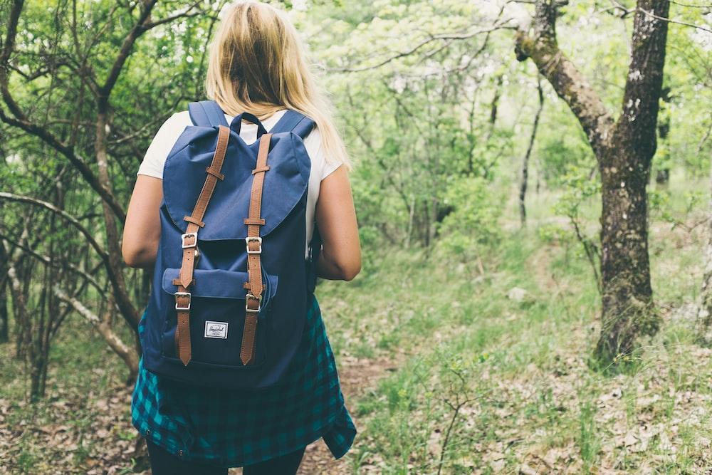 woman wearing backpack walking on forest
