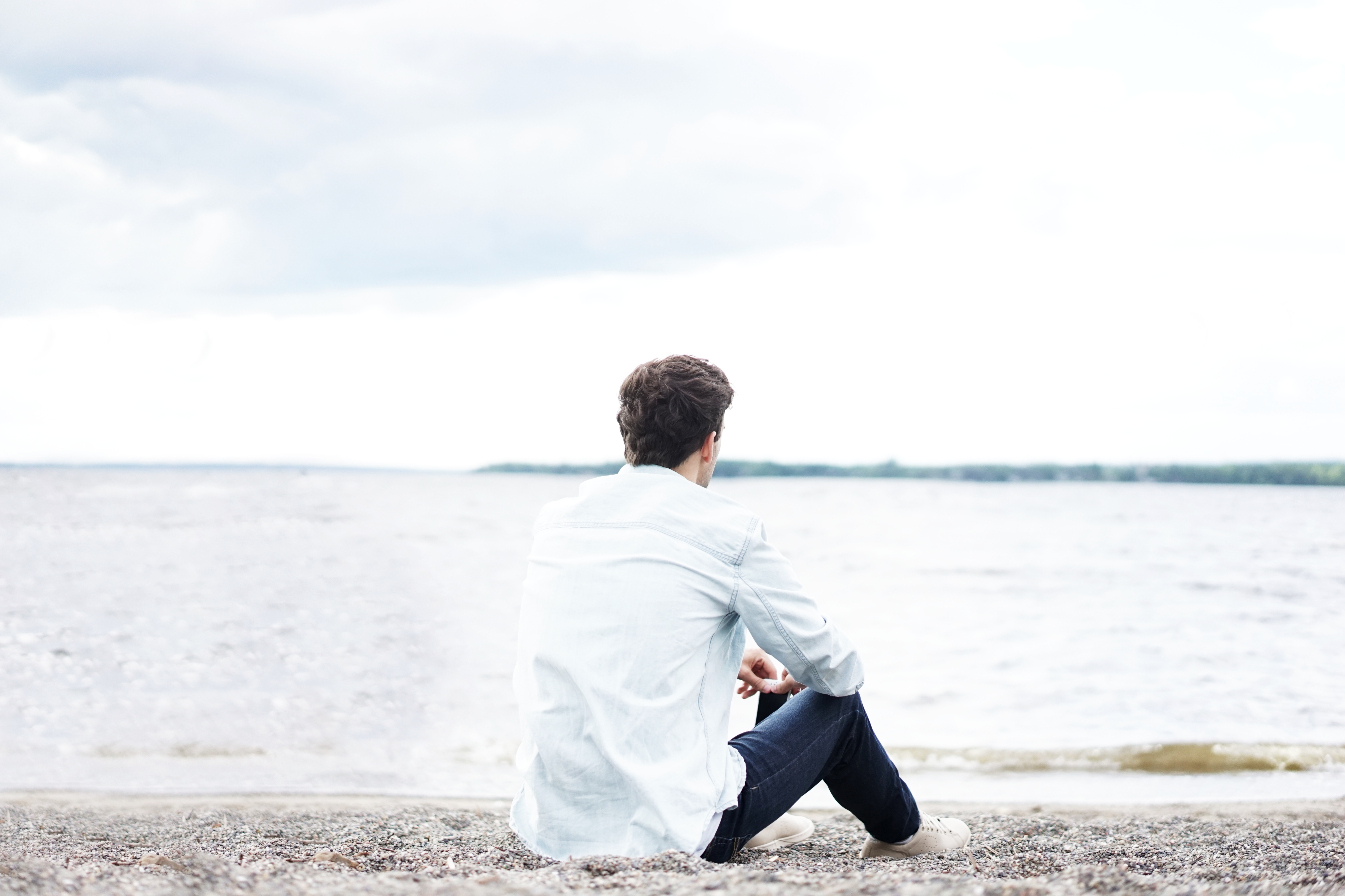 A man in a white shirt sitting on a pebble beach and looking of into the sea