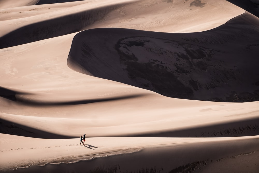 two person walking on desert during daytime