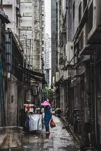 person carrying red bag in alley