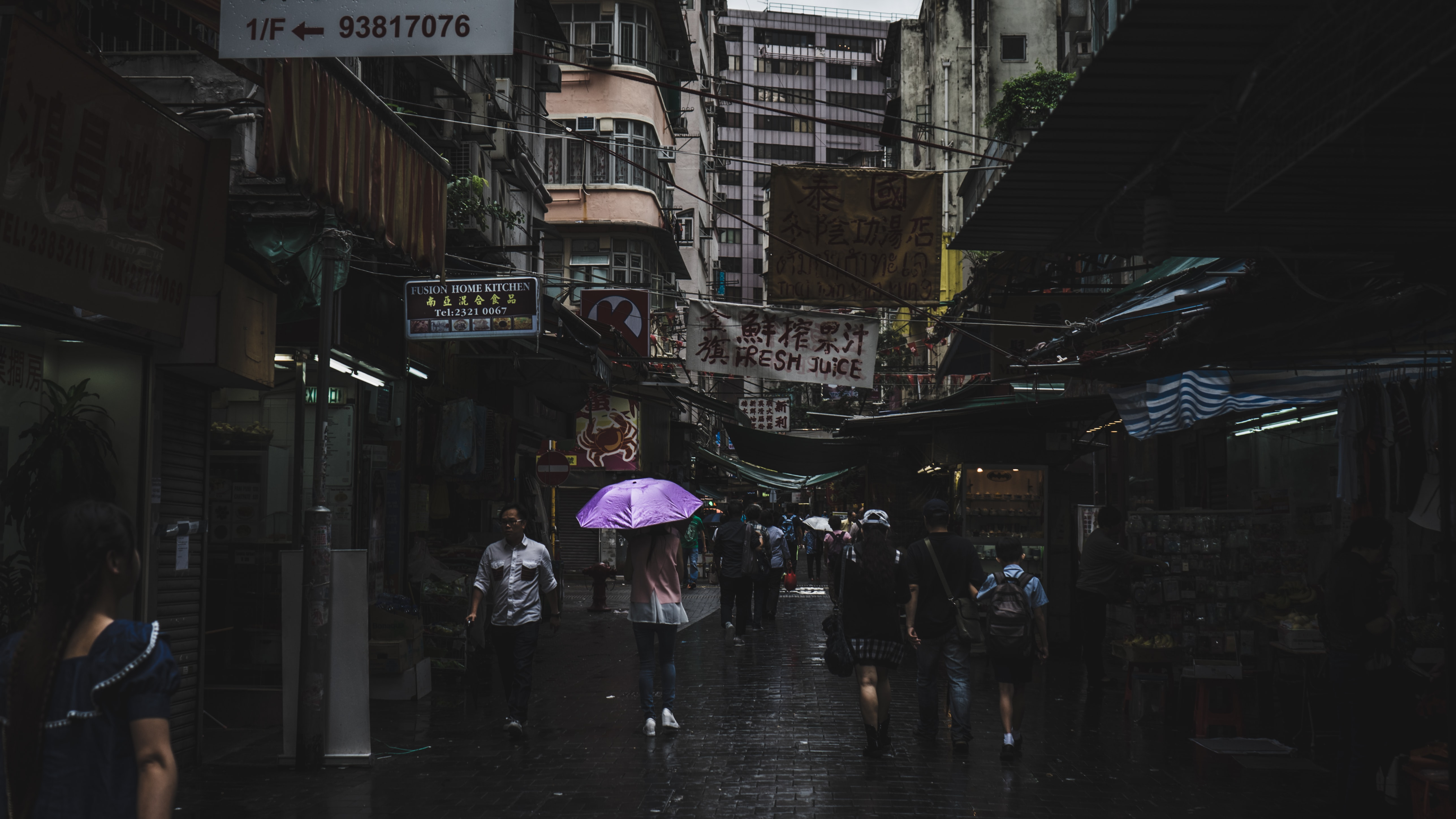 People walking in a narrow alley in Kowloon on a rainy day