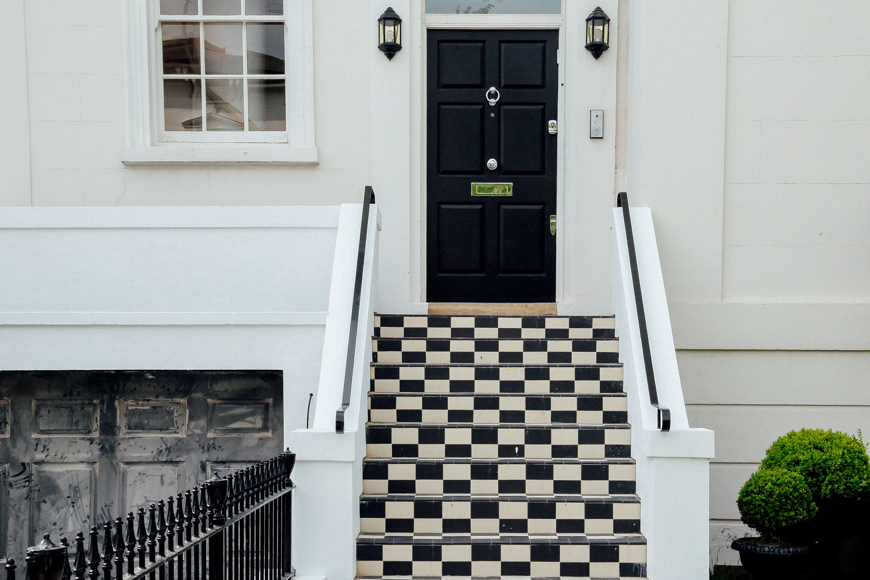 Checkered black and white residential outdoor stairway and black door in London