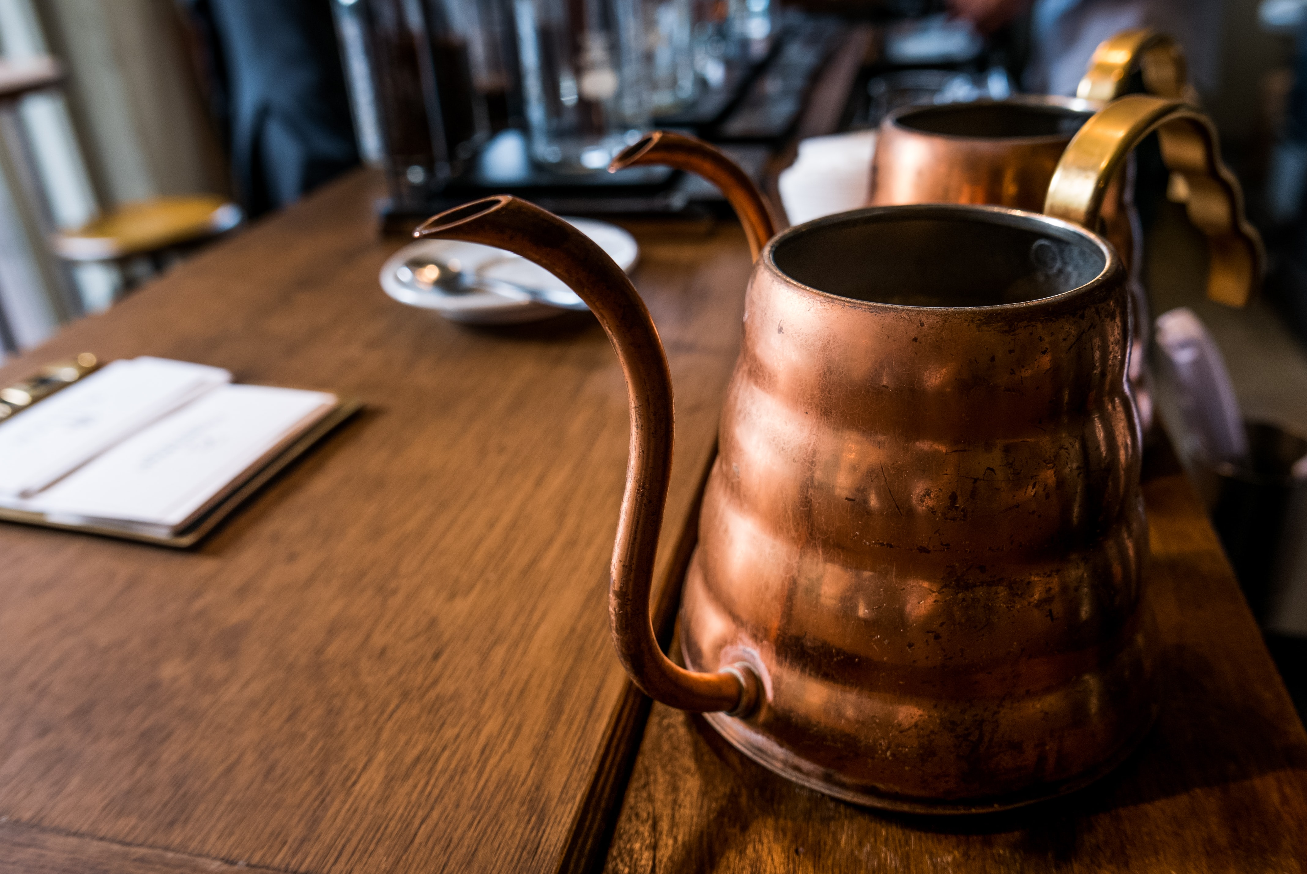 Copper tea kettles lined up on a wooden table with plates and menus alongside them