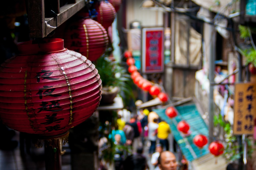 The macro view of Chinese lanterns placed on walls and a blurry view of people walking in a market road in jiufen old street.