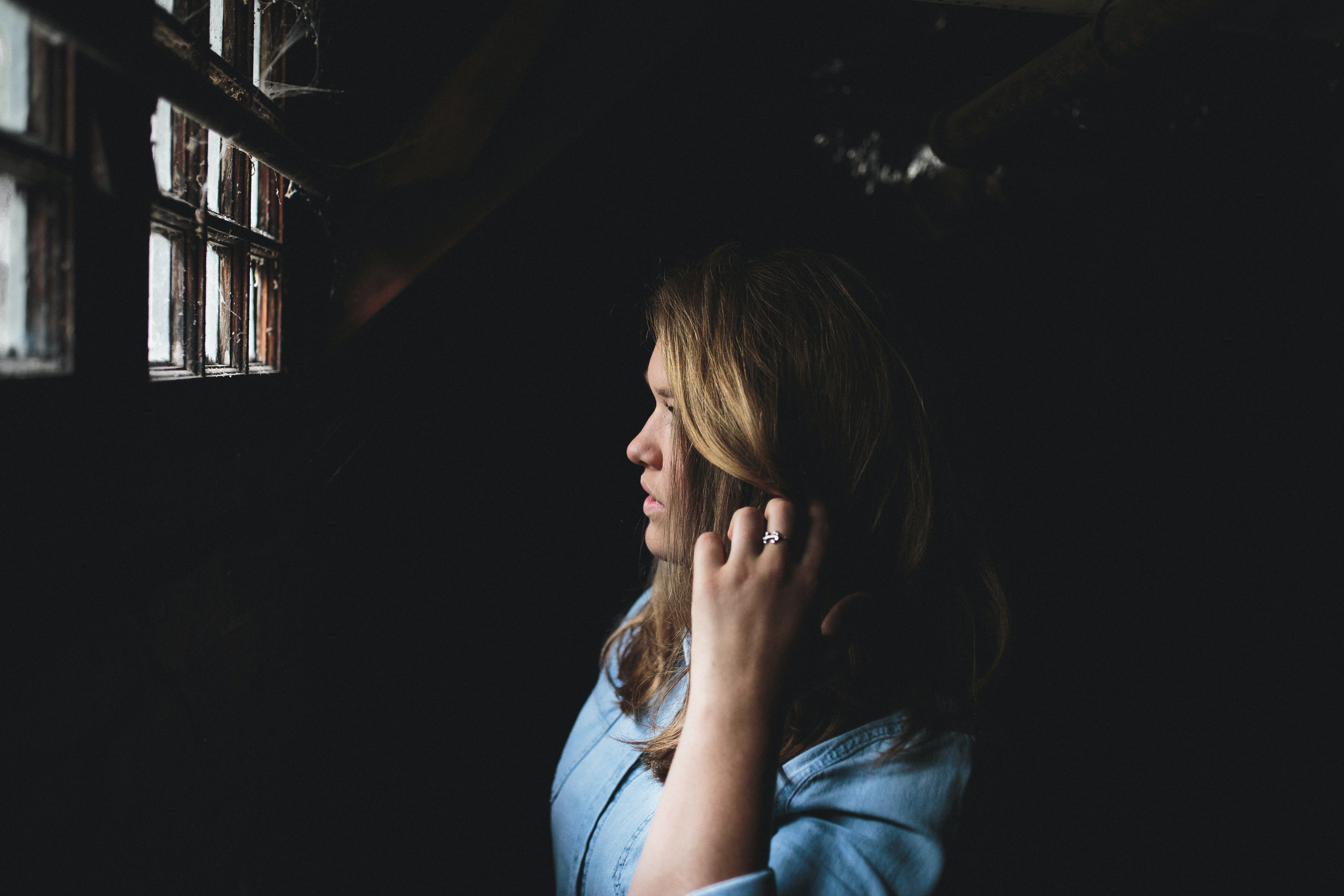 Woman with blonde hair wearing a blue shirt and ring looking out of a window covered in spider webs
