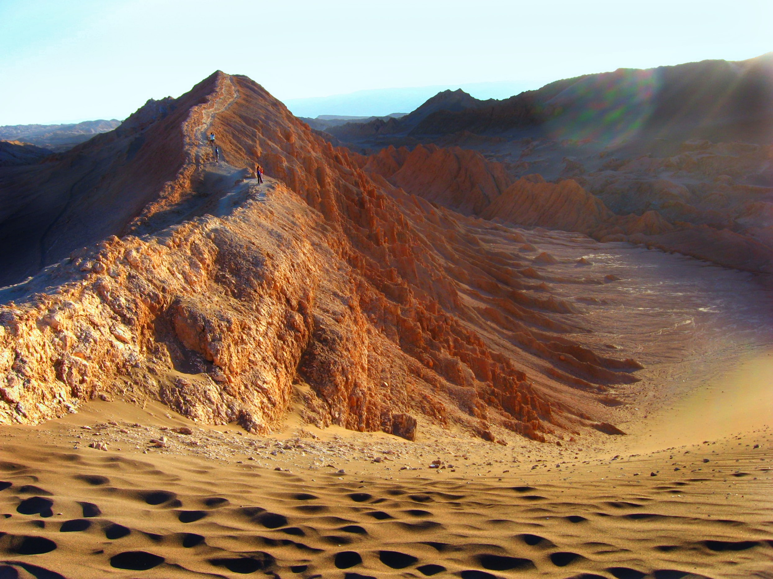 Hikers walk along sand ridges in the desert of Valle De La Luna