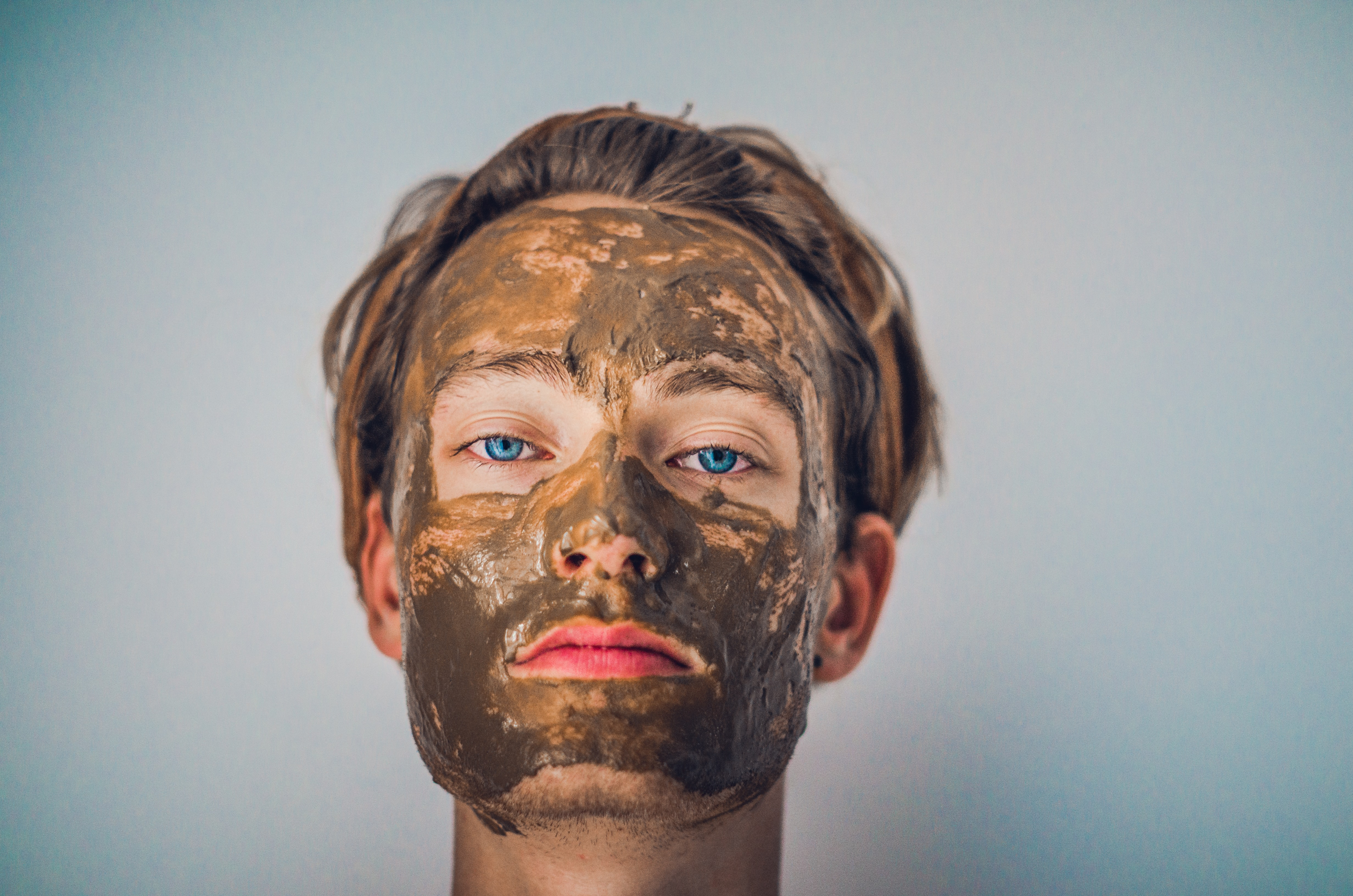 A blue-eyed man with a mud mask on his face