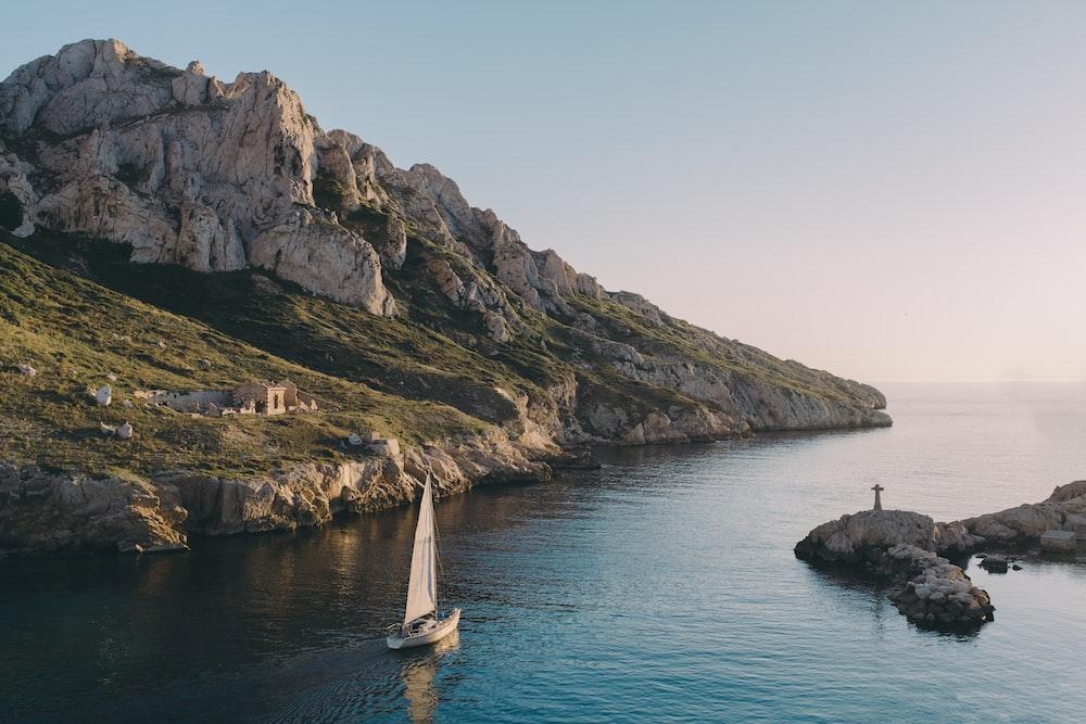 white sailboat near island rocks