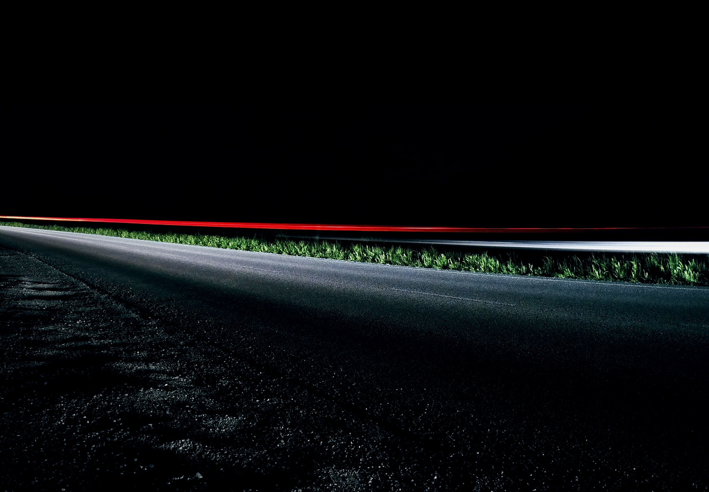 Time lapse red car light at night on road with asphalt and grass, Casale Sul Sile
