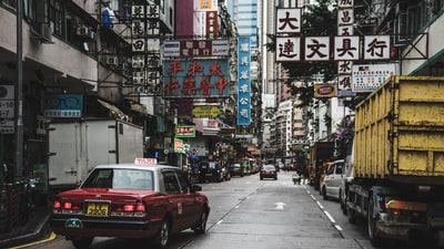 shini,red,toyota,taxi,drive,on,road,in,urban,street,with,advertis,sign,in,hong,kong