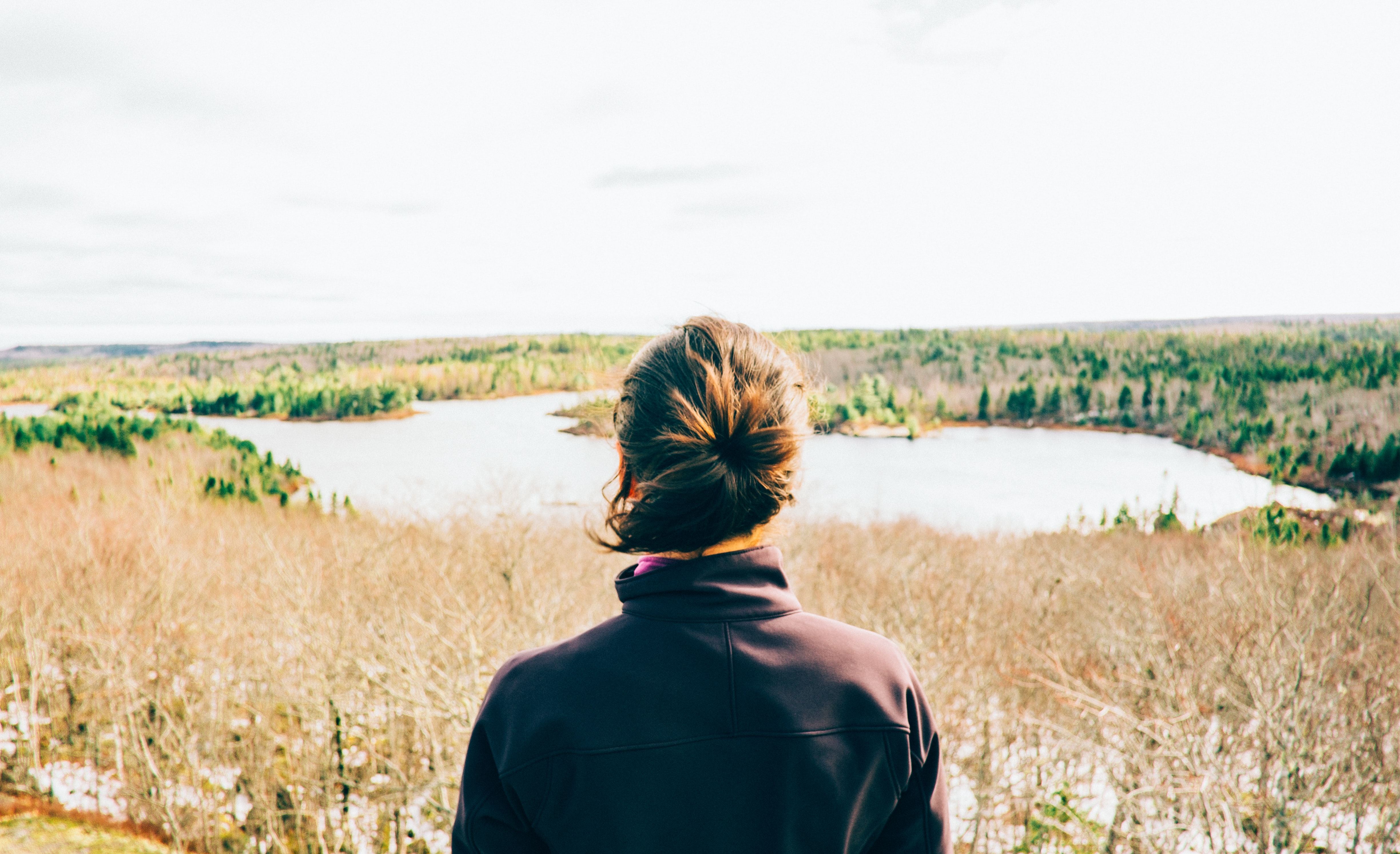 A woman with a ponytail wearing a jacket in a field of grass by a pond in Canada