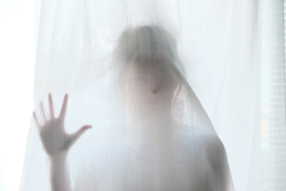 woman holding behind curtain