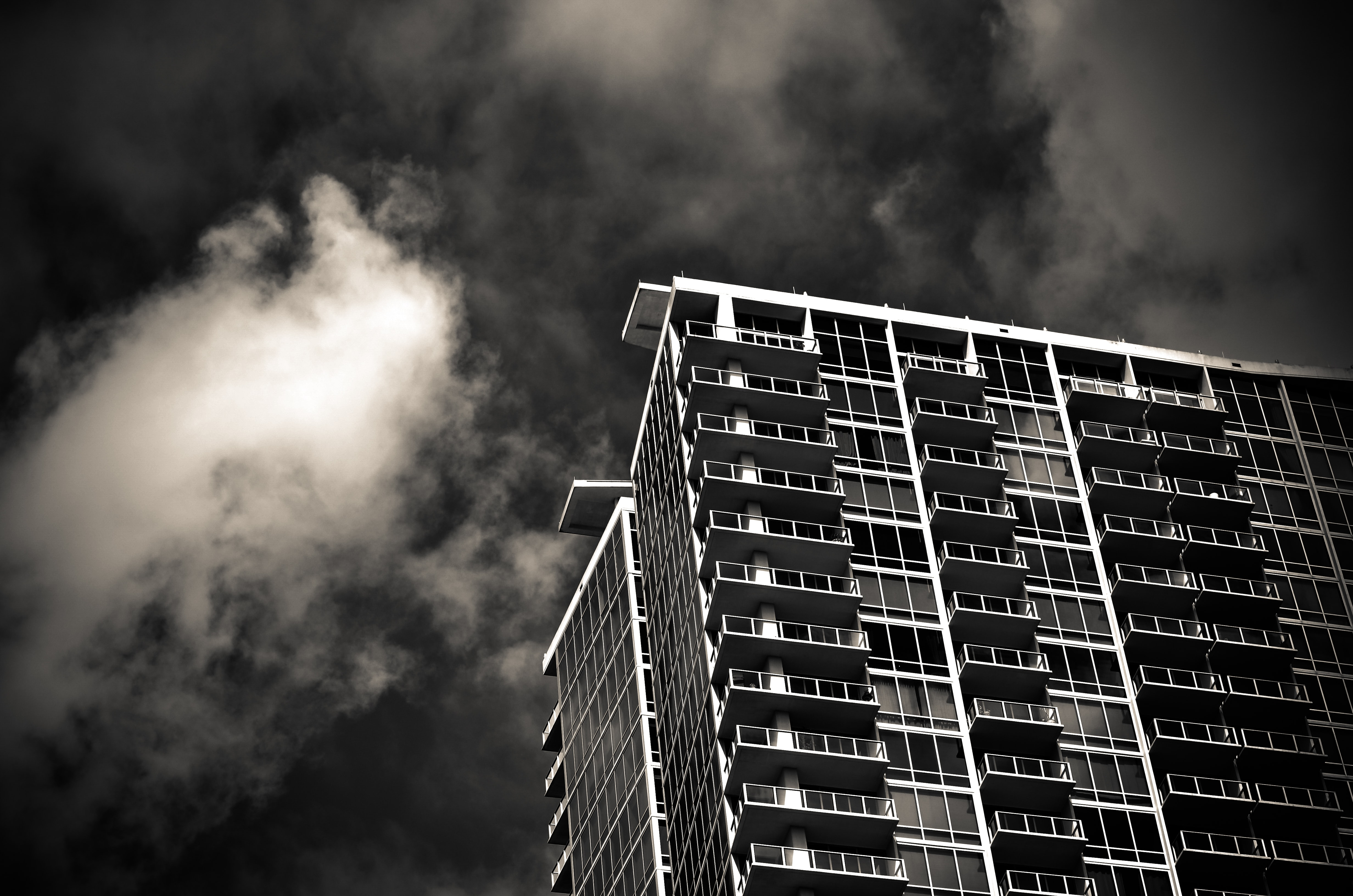Black and white shot of urban condo apartment building from below with clouds, Orlando