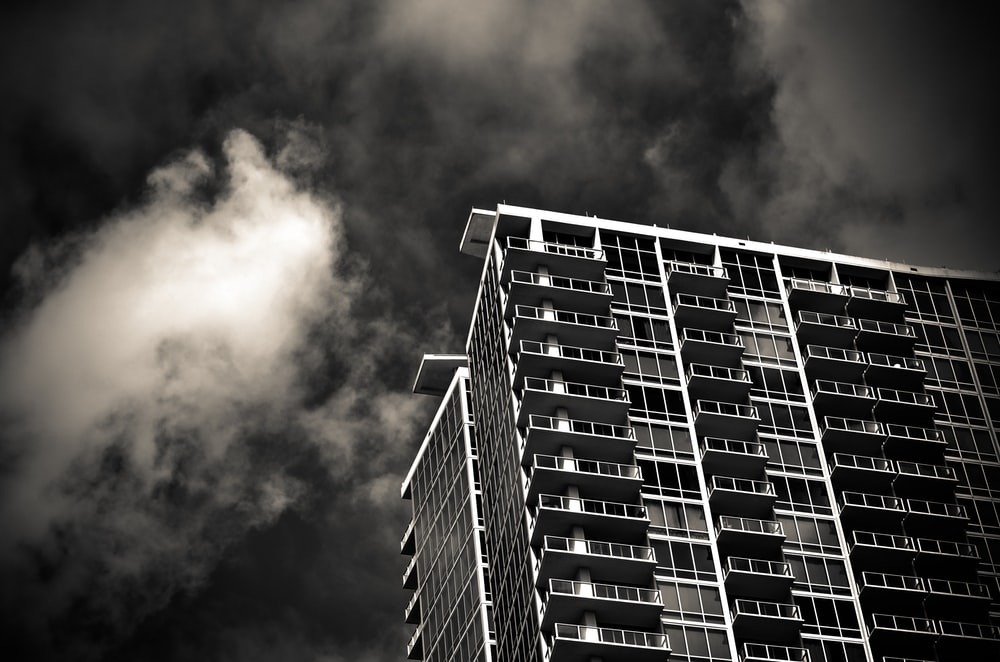 grayscale photography of building under cloudy sky