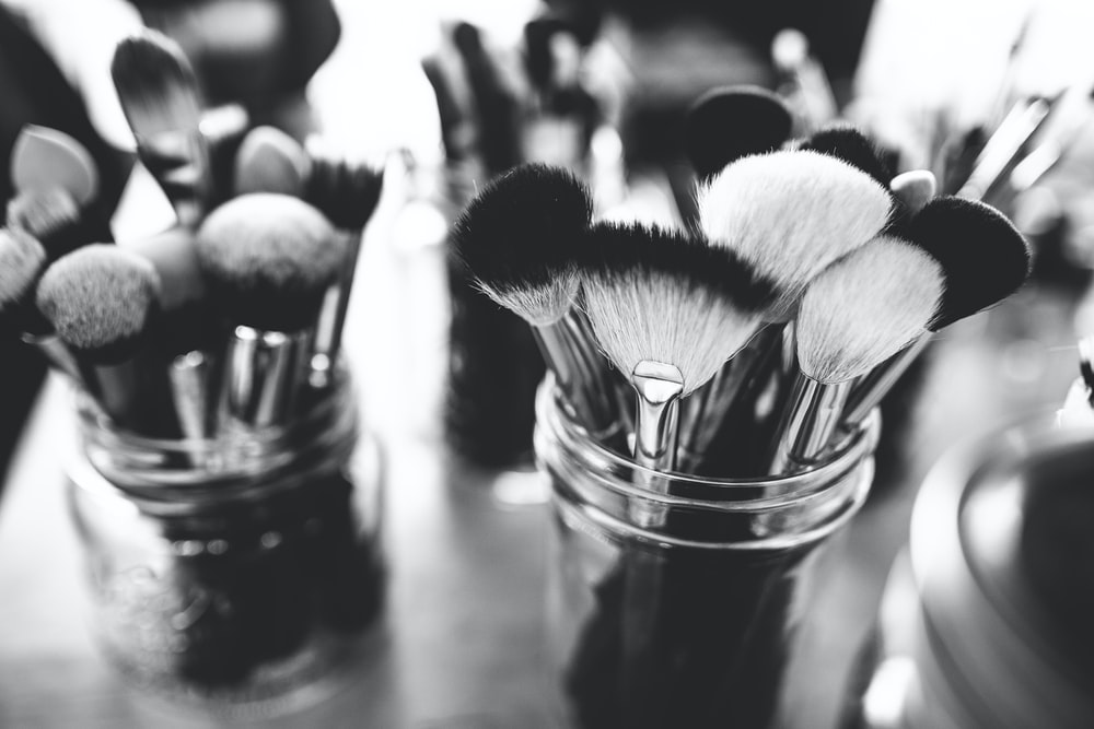 A black-and-white shot of make-up brushes in glass jars